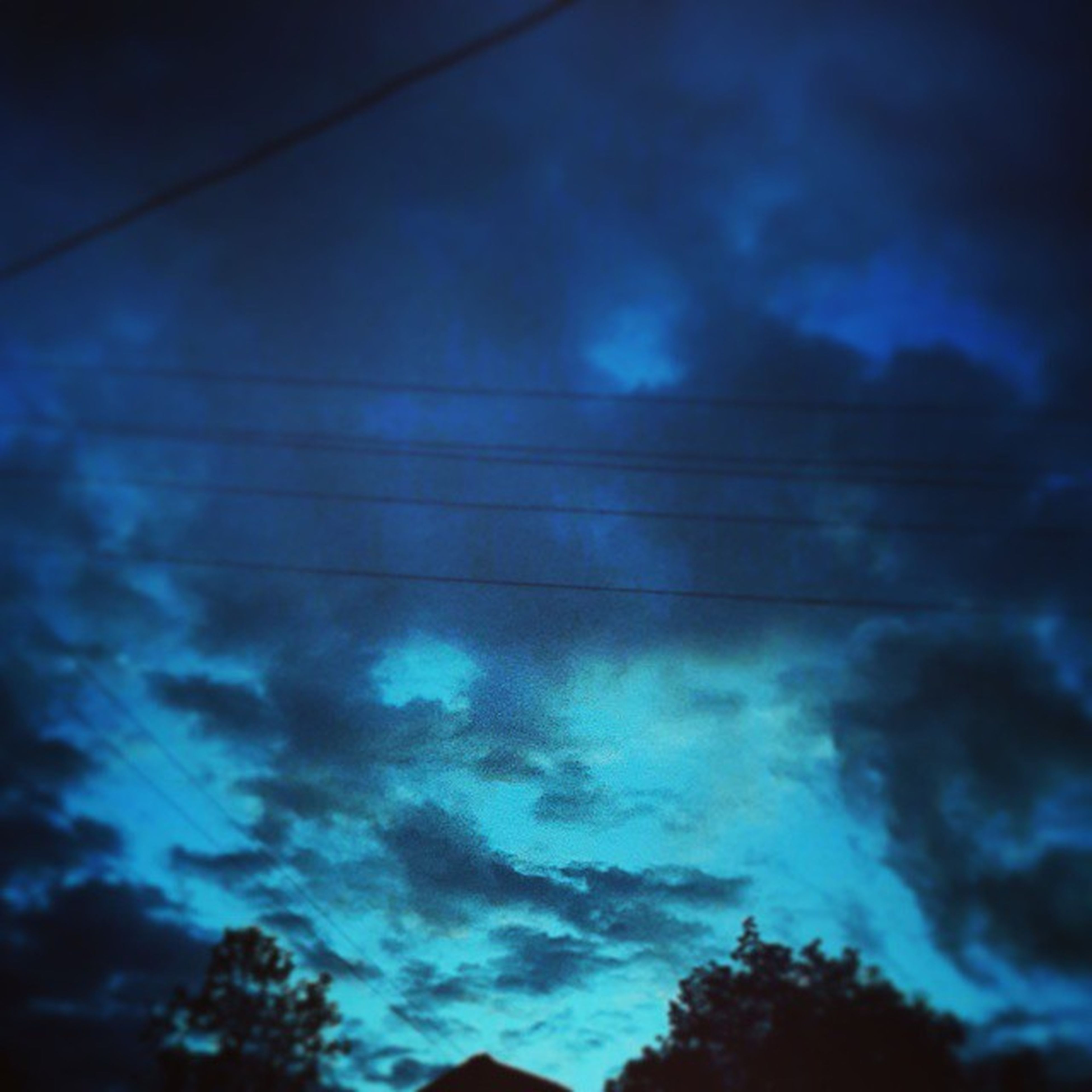 low angle view, sky, cloud - sky, cloudy, beauty in nature, blue, weather, cloud, nature, scenics, silhouette, tranquility, storm cloud, dusk, cloudscape, tranquil scene, overcast, dramatic sky, outdoors, power line