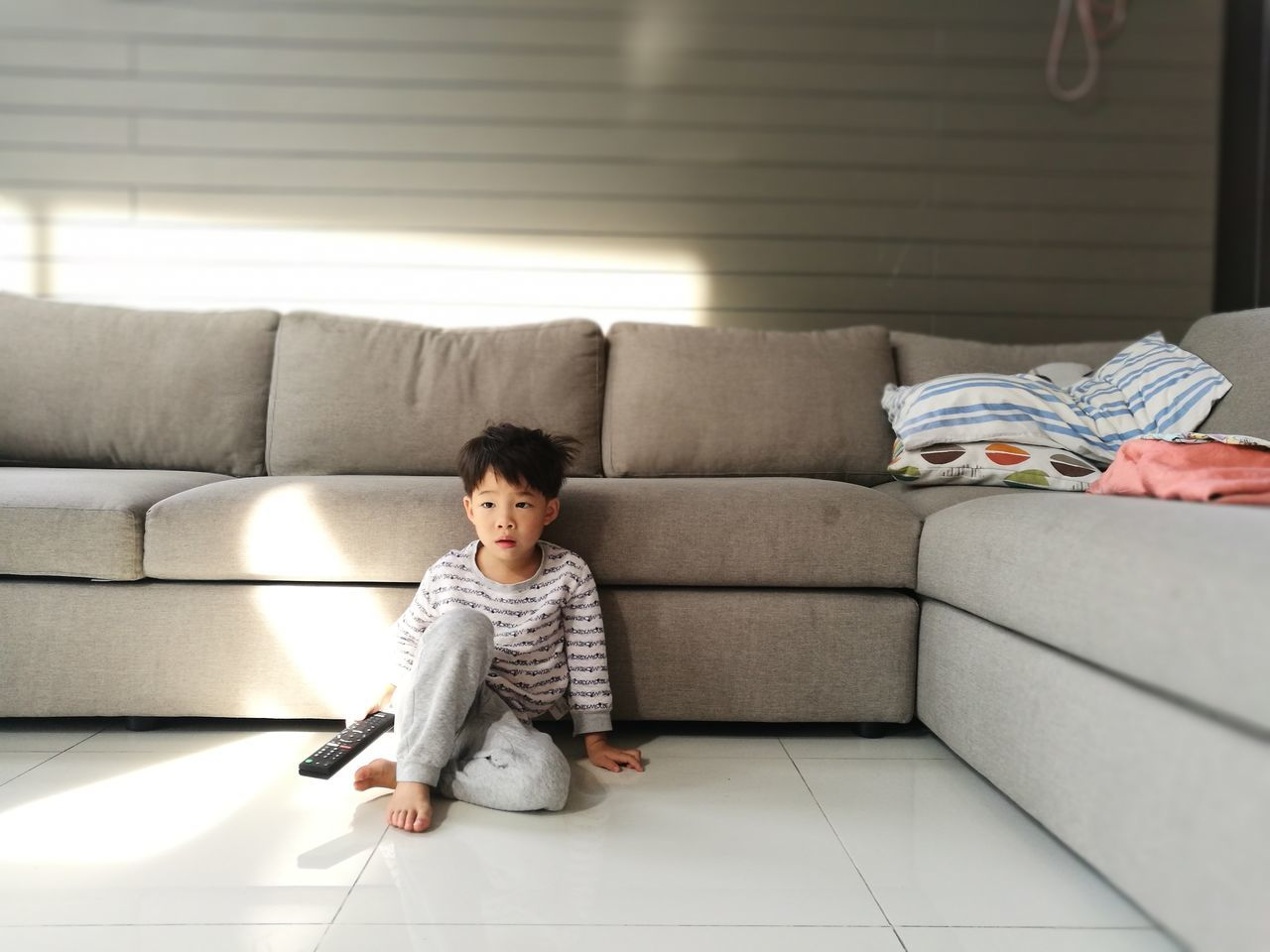 Sofa Living Room Indoors  One Person Sitting Casual Clothing Home Interior Domestic Life People Full Length Childhood Lifestyles Relaxation Happiness Barefoot Cute Smiling Candid Child Comfortable