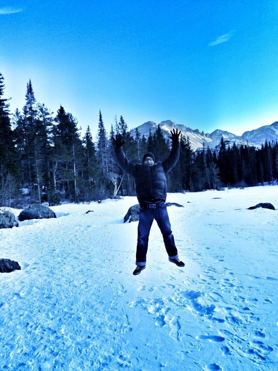 snow, winter, cold temperature, real people, leisure activity, one person, day, clear sky, weather, nature, blue, rear view, outdoors, lifestyles, full length, adventure, frozen, men, vacations, standing, scenics, beauty in nature, mountain, sky, warm clothing, snowboarding, tree, people
