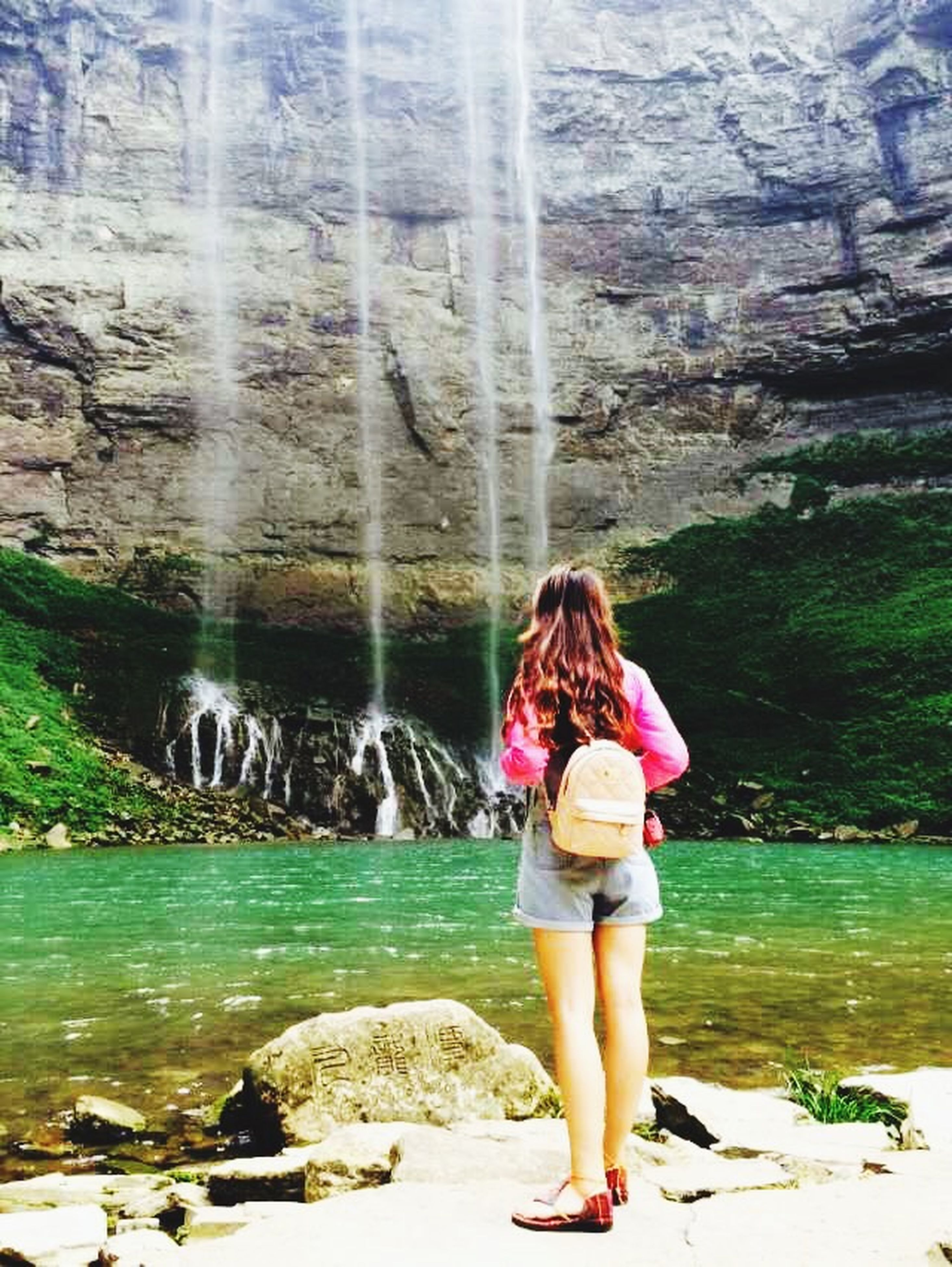 water, full length, lifestyles, rear view, leisure activity, casual clothing, standing, girls, person, nature, childhood, day, three quarter length, young women, rock - object, vacations, beauty in nature