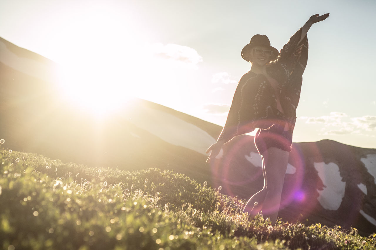 lens flare, sunlight, sunbeam, sun, nature, sky, leisure activity, outdoors, sunny, real people, field, grass, lifestyles, full length, sunset, day, vacations, young women, beauty in nature, two people, standing, landscape, women, childhood, mountain, young adult, people