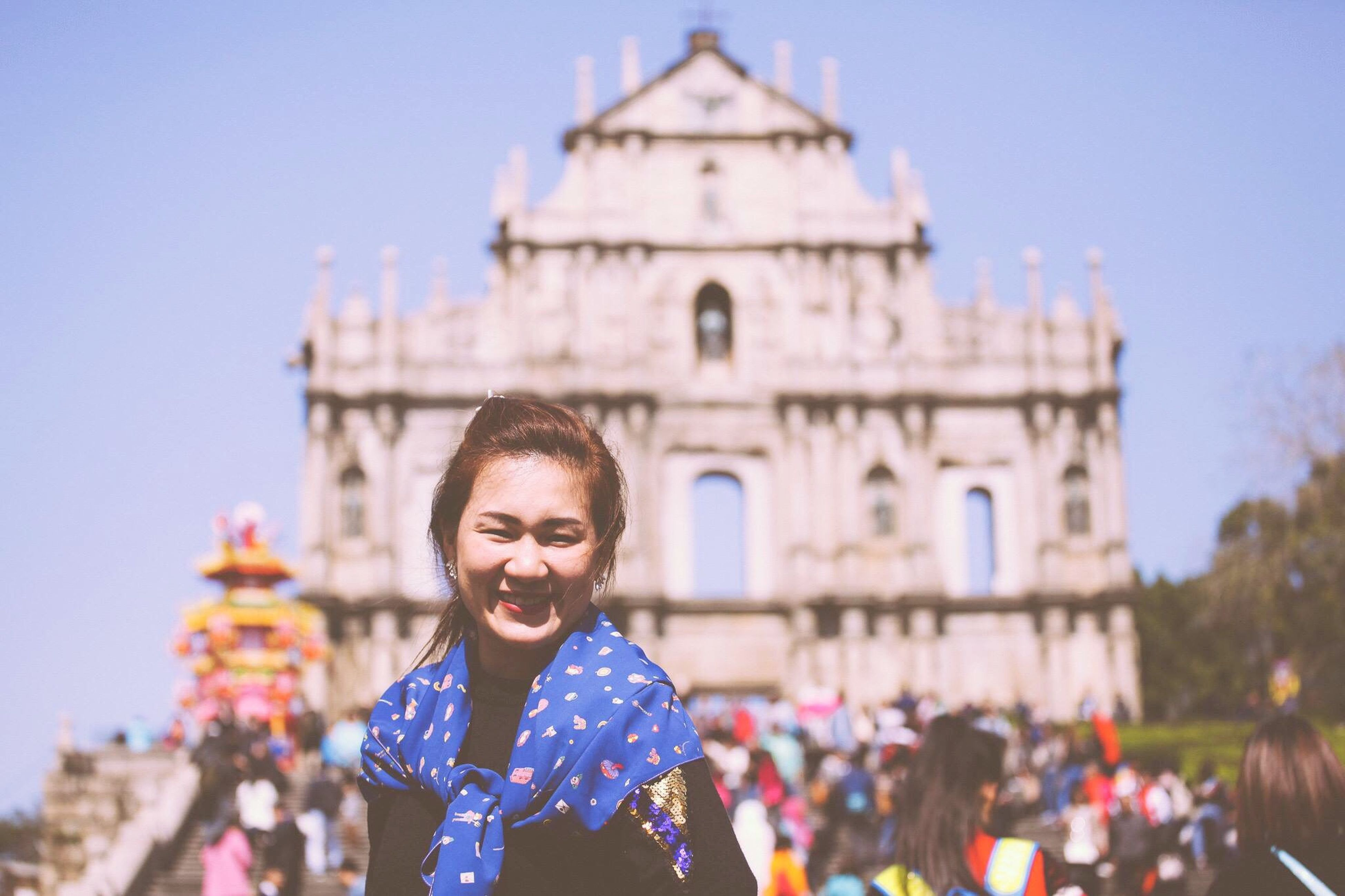 lifestyles, person, architecture, building exterior, leisure activity, portrait, looking at camera, built structure, young adult, smiling, front view, happiness, focus on foreground, casual clothing, headshot, religion, standing