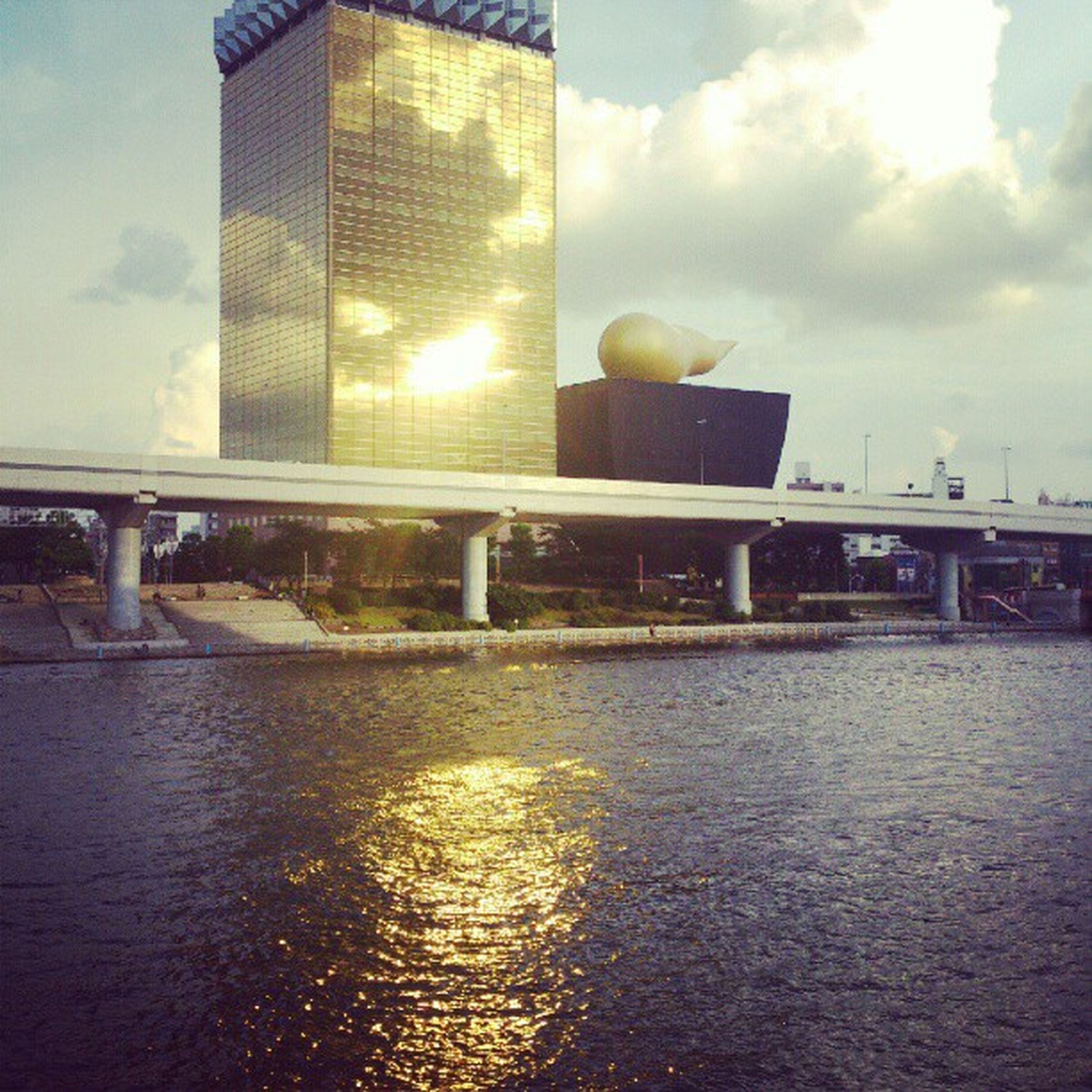 architecture, built structure, building exterior, water, sky, waterfront, reflection, city, cloud - sky, river, building, sun, sunlight, sunbeam, no people, lens flare, cloud, outdoors, rippled, modern