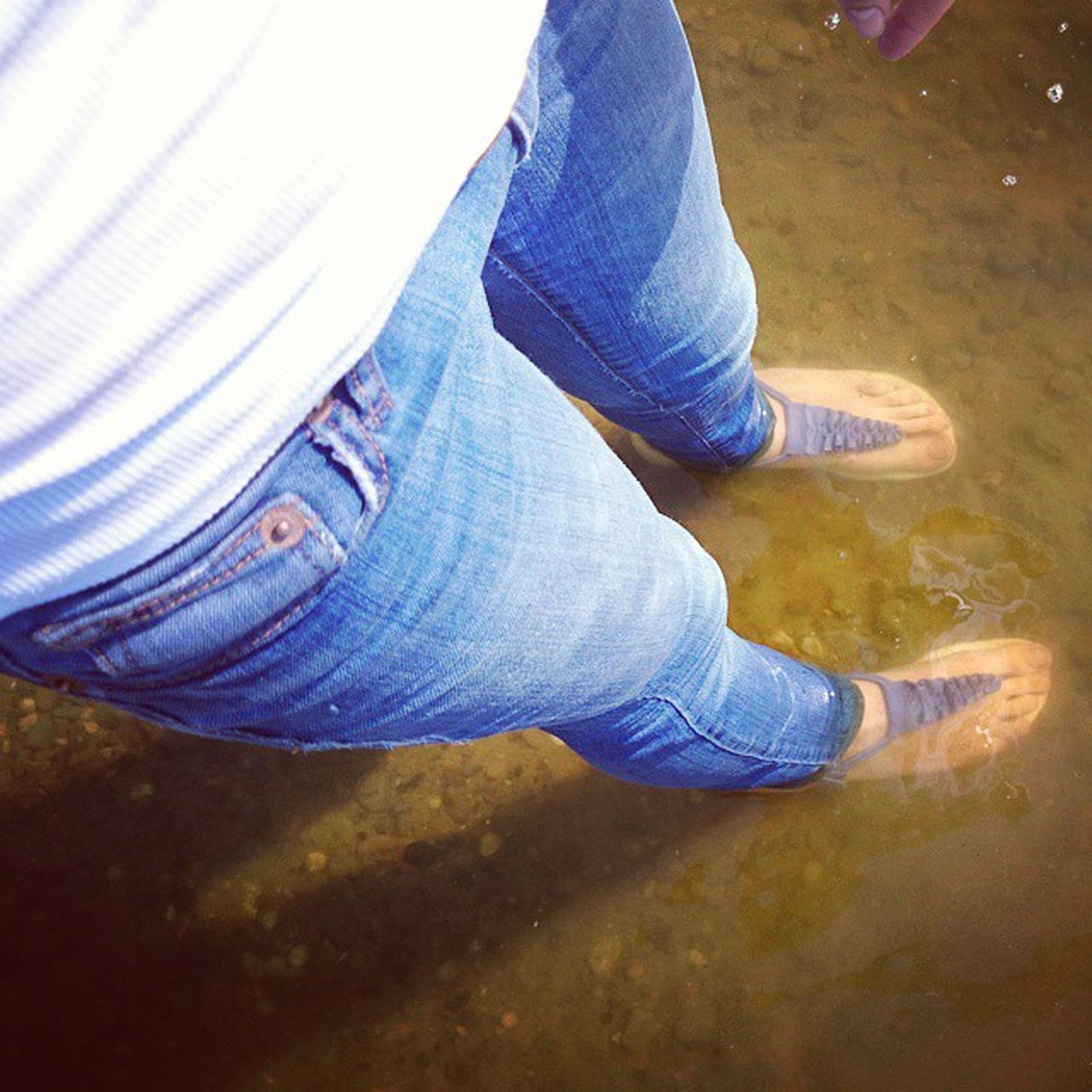 low section, person, jeans, shoe, lifestyles, casual clothing, leisure activity, standing, men, footwear, blue, human foot, high angle view, day, outdoors, unrecognizable person, field