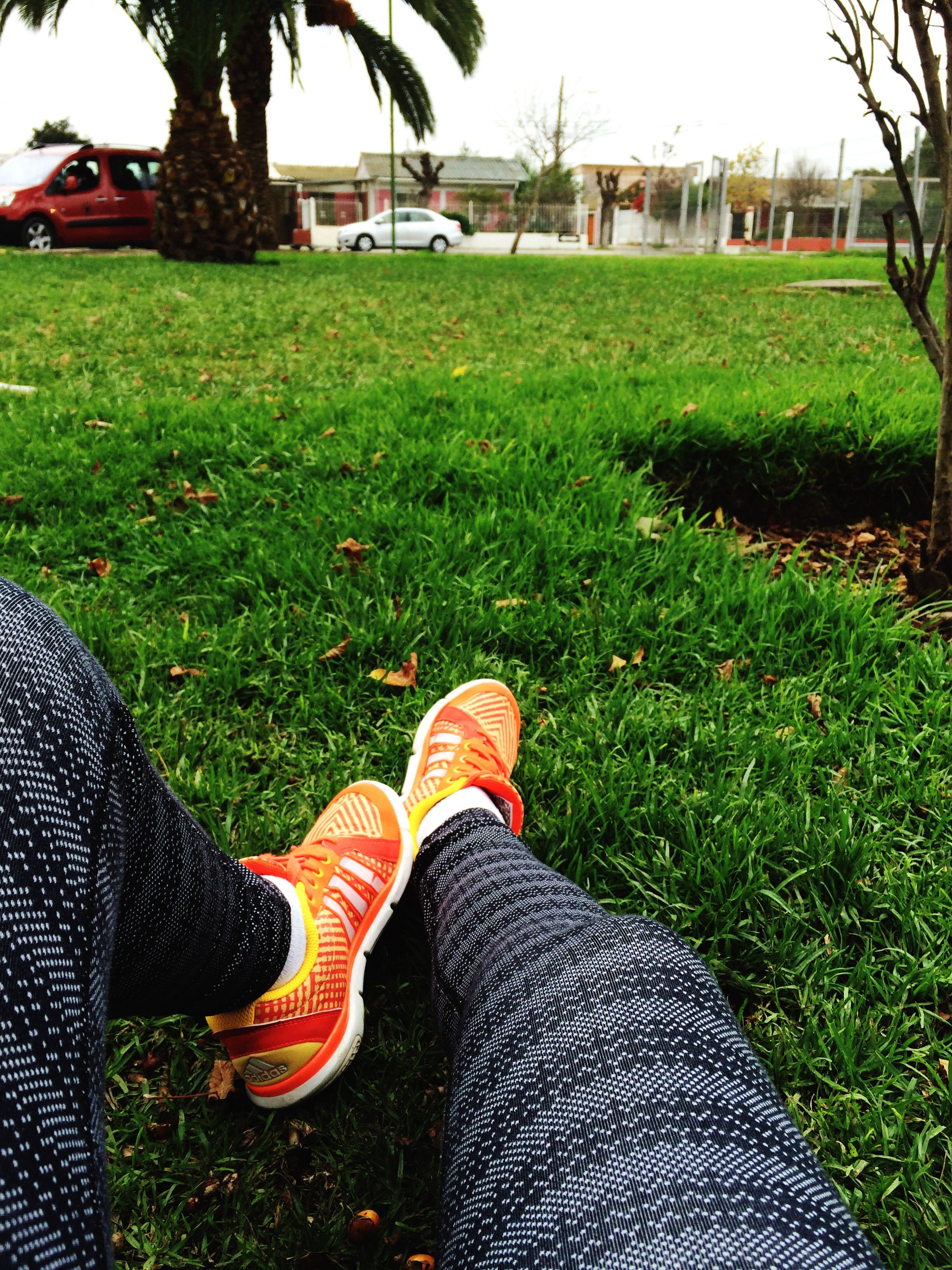 grass, low section, person, shoe, grassy, field, lawn, relaxation, green color, personal perspective, footwear, leisure activity, park - man made space, sitting, resting, lifestyles, day