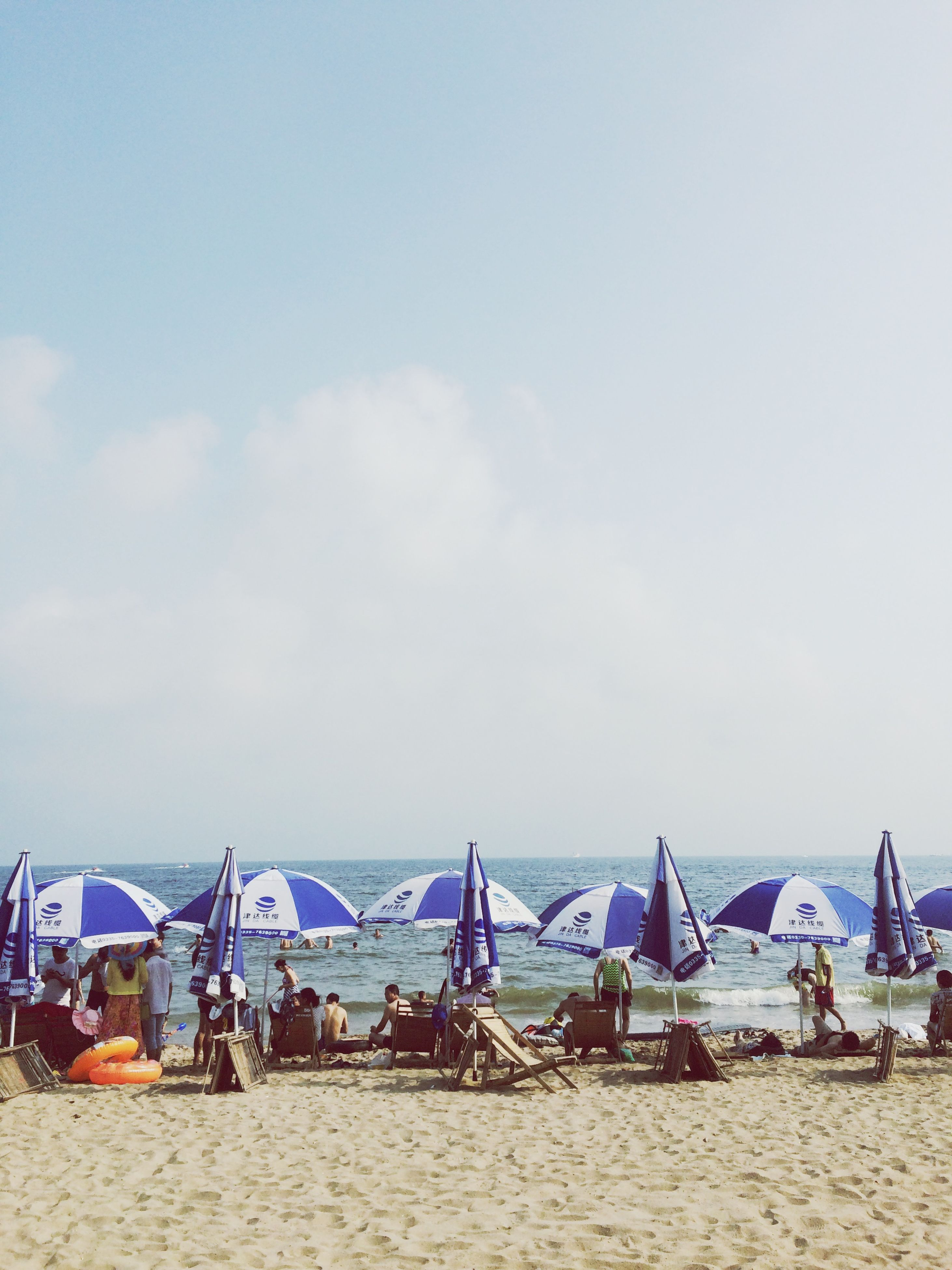 beach, sand, sea, shore, sky, beach umbrella, horizon over water, vacations, large group of people, parasol, relaxation, sunshade, summer, copy space, day, nature, leisure activity, water, blue