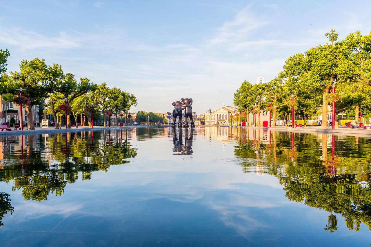 water, reflection, tree, sky, waterfront, outdoors, day, nature, built structure, architecture, beauty in nature, lake, tranquility, cloud - sky, real people, vacations, travel destinations, men, building exterior, scenics, people