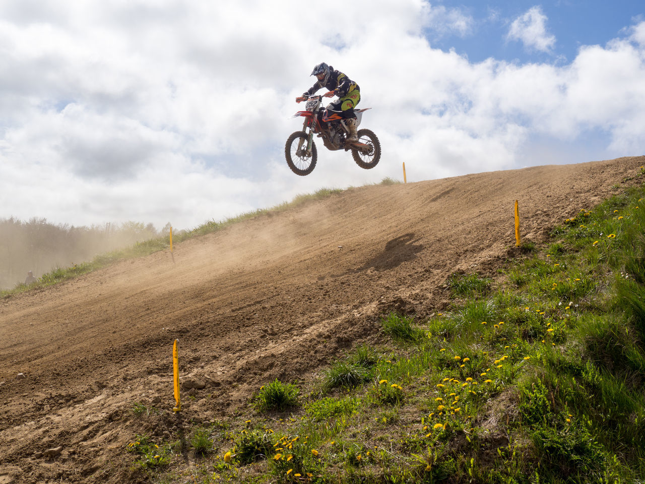 motocross, sports race, real people, extreme sports, motorsport, motorcycle, men, crash helmet, land vehicle, mid-air, speed, off-road vehicle, mode of transport, riding, cloud - sky, sky, adventure, one person, competitive sport, field, motorcycle racing, transportation, day, outdoors, sports track, leisure activity, stunt, sports clothing, sport, jumping, competition, lifestyles, headwear, helmet, professional sport, biker, people