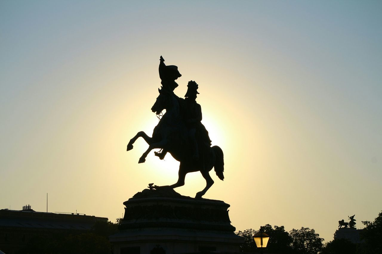 statue, sculpture, human representation, sunset, male likeness, horse, silhouette, monument, art and craft, history, architecture, low angle view, travel destinations, outdoors, horseback riding, built structure, sky, memorial, king - royal person, clear sky, tourism, building exterior, no people, city, tree, day