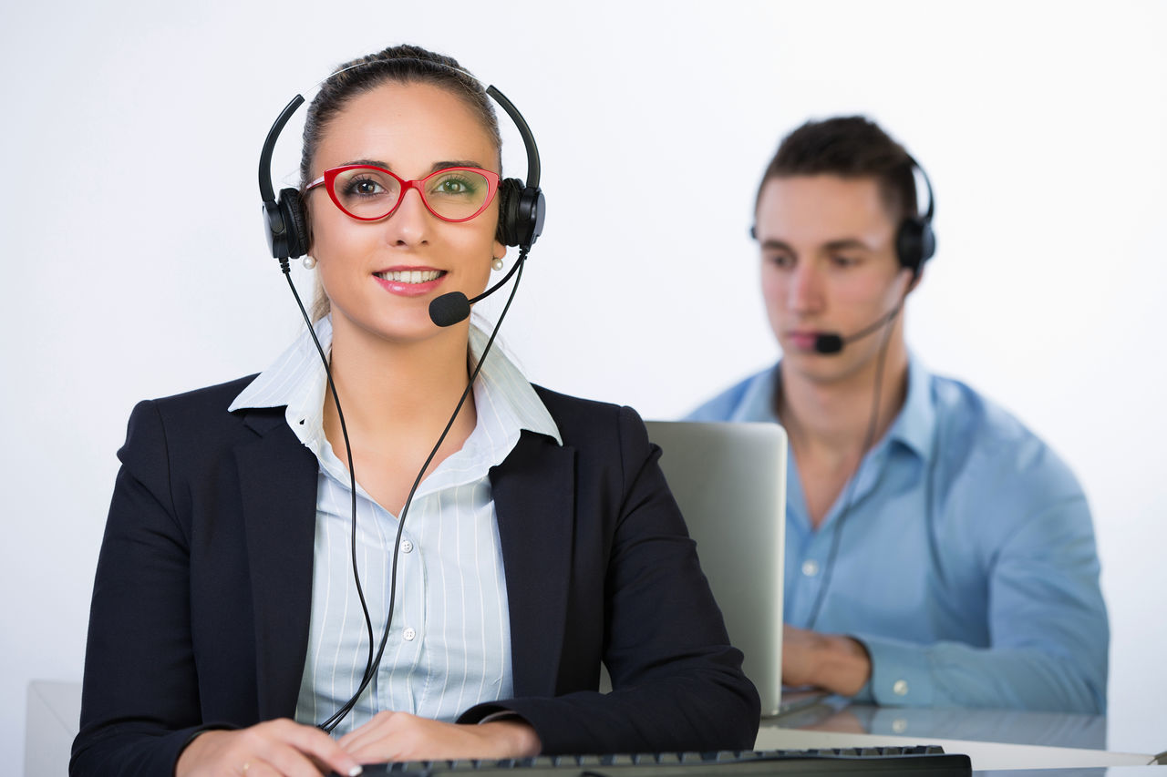 technology, young adult, communication, using phone, front view, young women, wireless technology, listening, connection, headset, businesswoman, indoors, customer service representative, two people, business, office, working, it support, eyeglasses, sitting, smiling, day