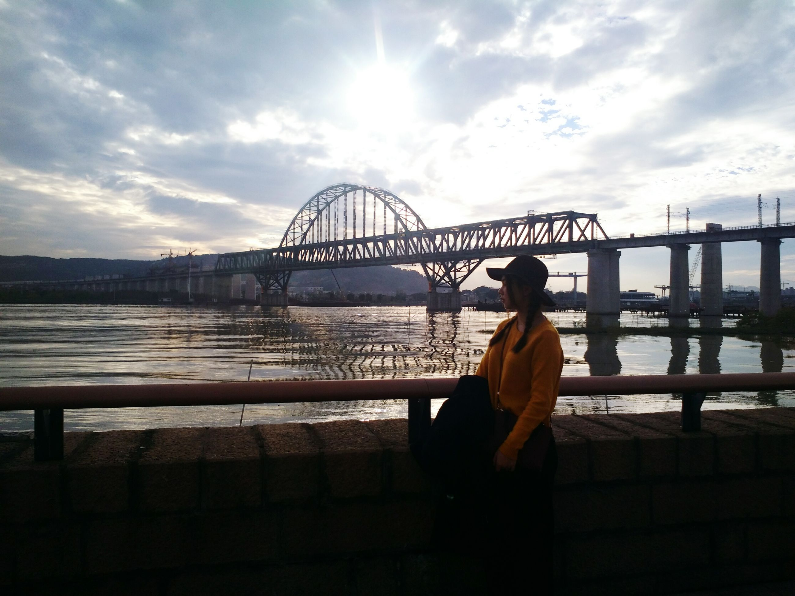 bridge - man made structure, one man only, sky, sunset, sun, river, outdoors, rear view, silhouette, idyllic, one person, men, beauty in nature, architecture, adults only, water, people, only men, railway bridge, day, adult