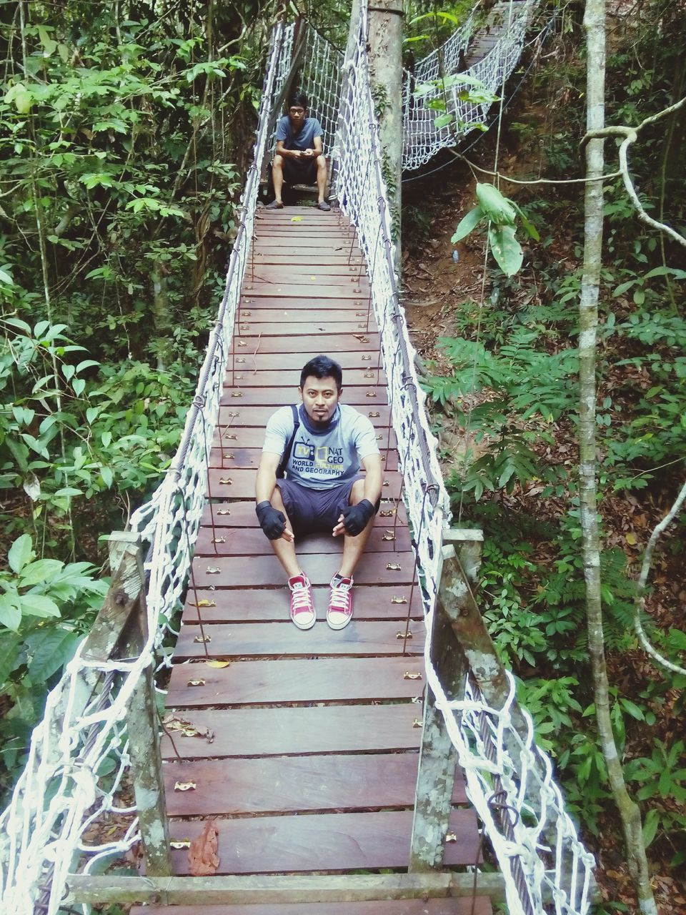 full length, real people, steps, leisure activity, one person, front view, railing, stairs, footbridge, young adult, lifestyles, forest, smiling, outdoors, steps and staircases, casual clothing, tree, looking at camera, young women, bridge - man made structure, day, plant, portrait, growth, happiness, nature, climbing, architecture, people