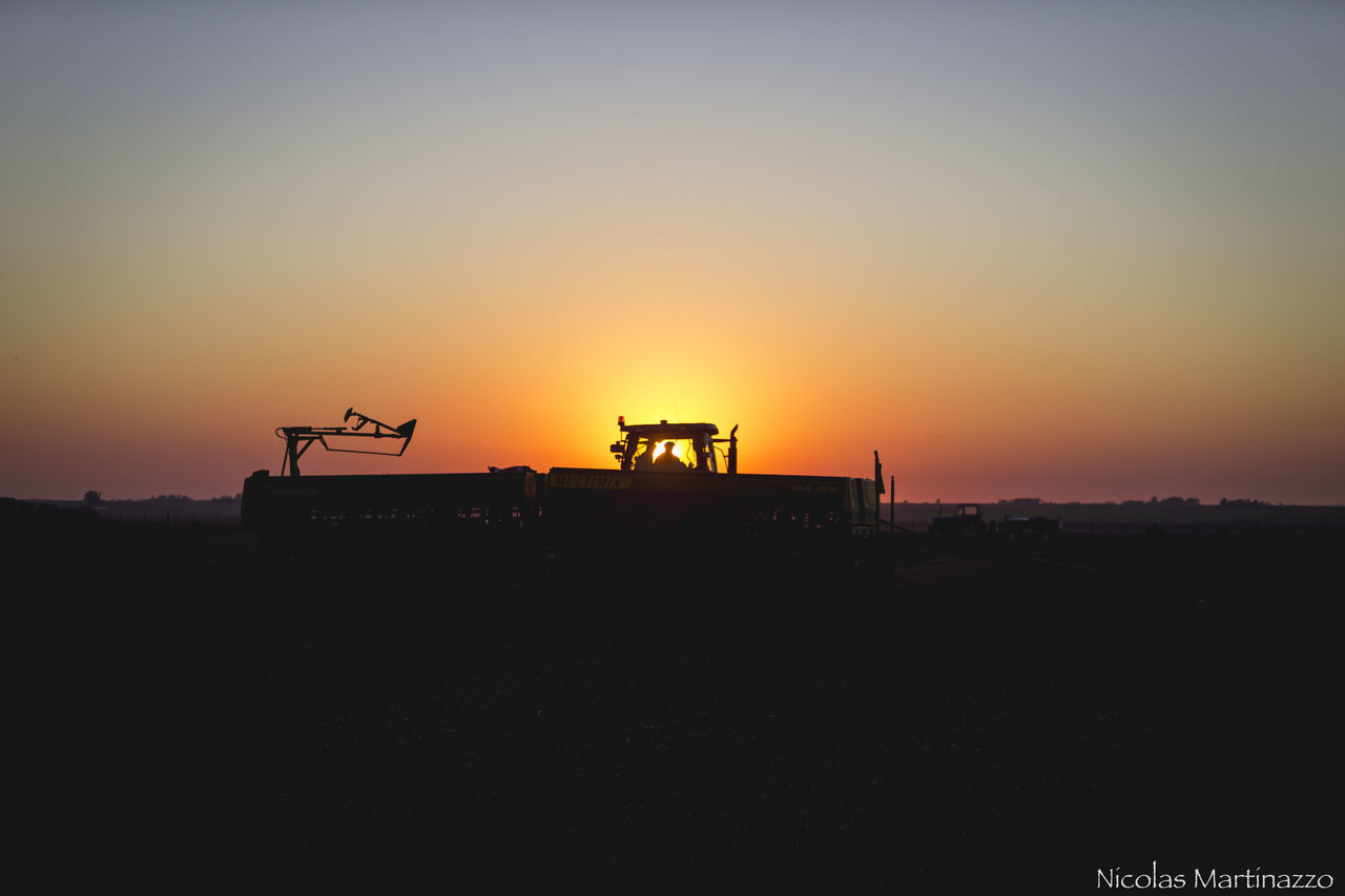 sunset, silhouette, orange color, sky, construction site, nature, outdoors, built structure, architecture, clear sky, building exterior, no people, drilling rig, day, oil pump