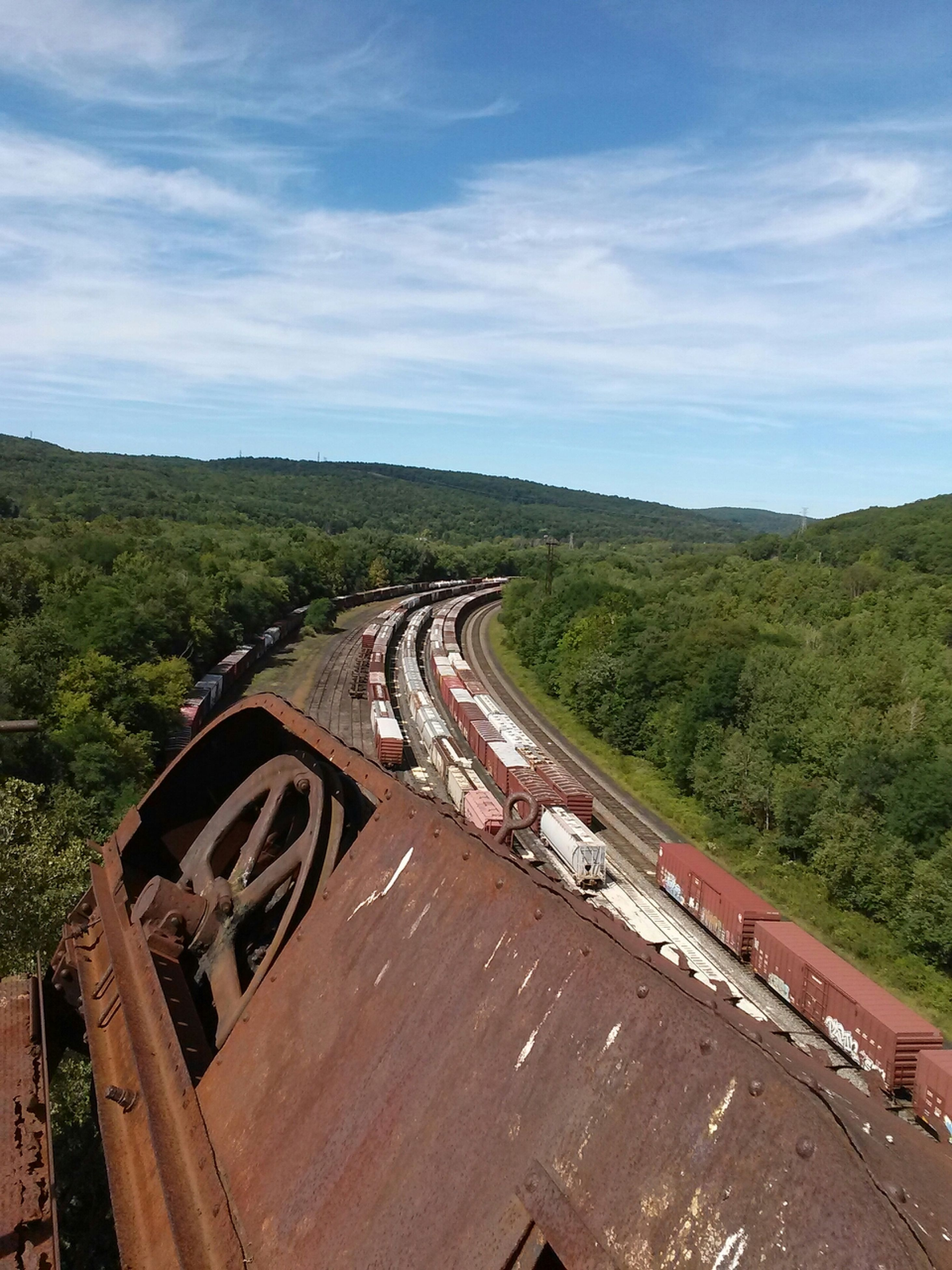 transportation, sky, cloud - sky, high angle view, landscape, railroad track, road, tree, cloud, built structure, rail transportation, cloudy, the way forward, nature, diminishing perspective, day, architecture, outdoors, green color, vanishing point