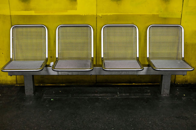 Bench Day Dirty Empty Front View Green Color Have A Seat In A Row Metal No People Outdoors PaintJob Platform Public Transportation Rail Transportation Rest Seat Symmetry Transportation Wall Yellow