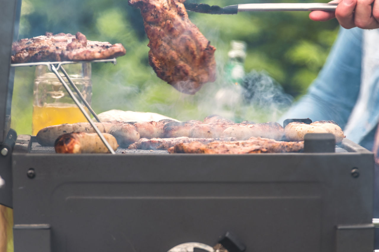 Barbecue Barbecue Grill Day Food Food And Drink Freshness Grilled Heat - Temperature Human Body Part Human Hand Meat Men One Person Outdoors Party - Social Event People Preparation  Preparing Food Red Meat Roasted Sausage Serving Tongs Smoke - Physical Structure