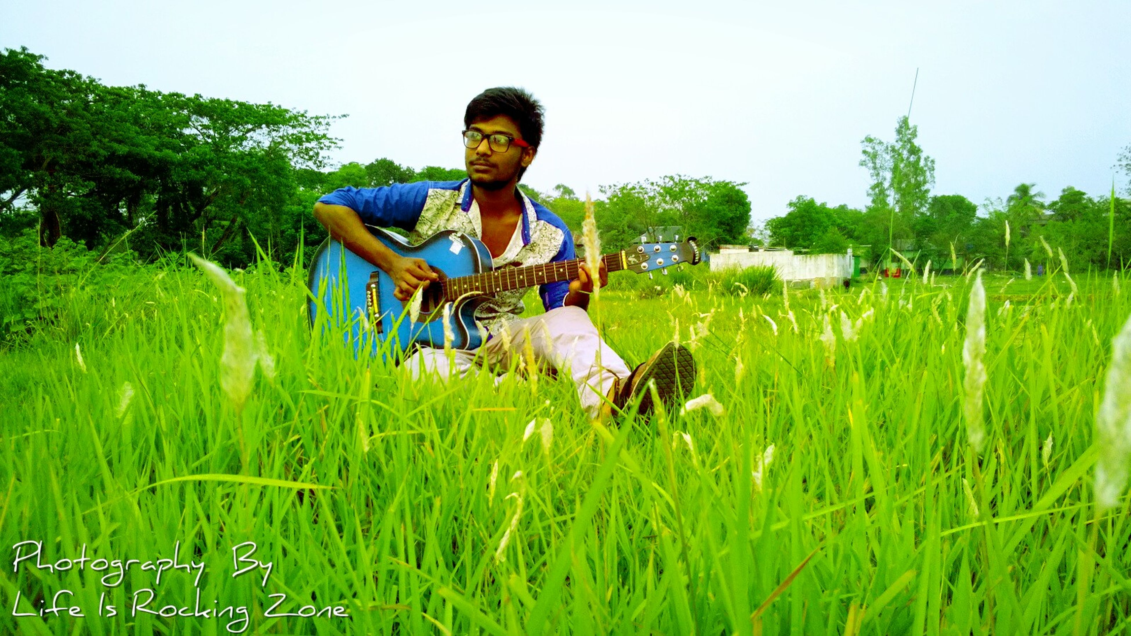 grass, leisure activity, full length, lifestyles, young adult, casual clothing, person, field, grassy, tree, green color, growth, young men, sky, fun, plant, enjoyment