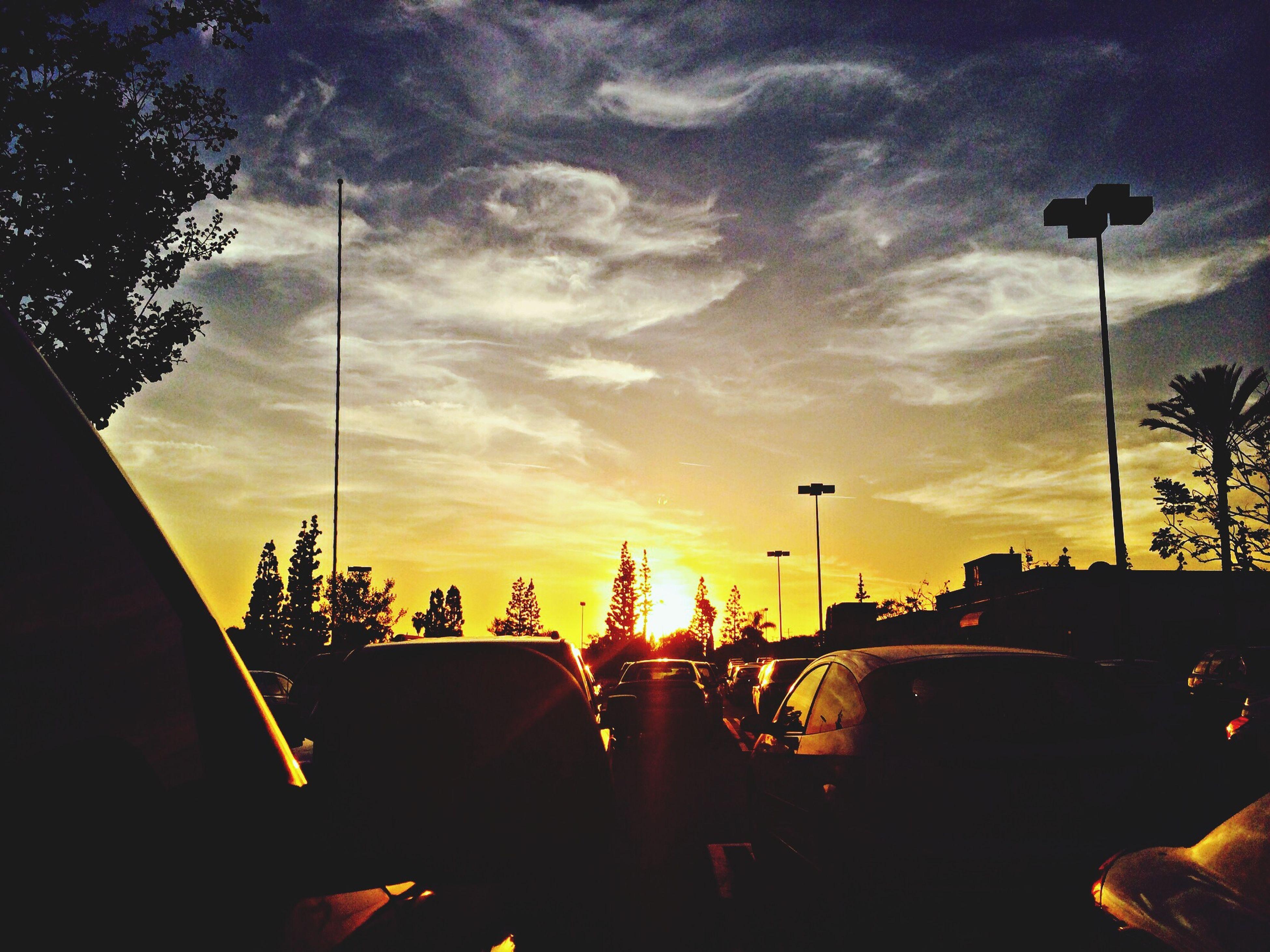 transportation, car, land vehicle, sunset, mode of transport, sky, street light, silhouette, road, street, tree, cloud - sky, traffic, orange color, illuminated, dusk, on the move, cloud, outdoors, travel