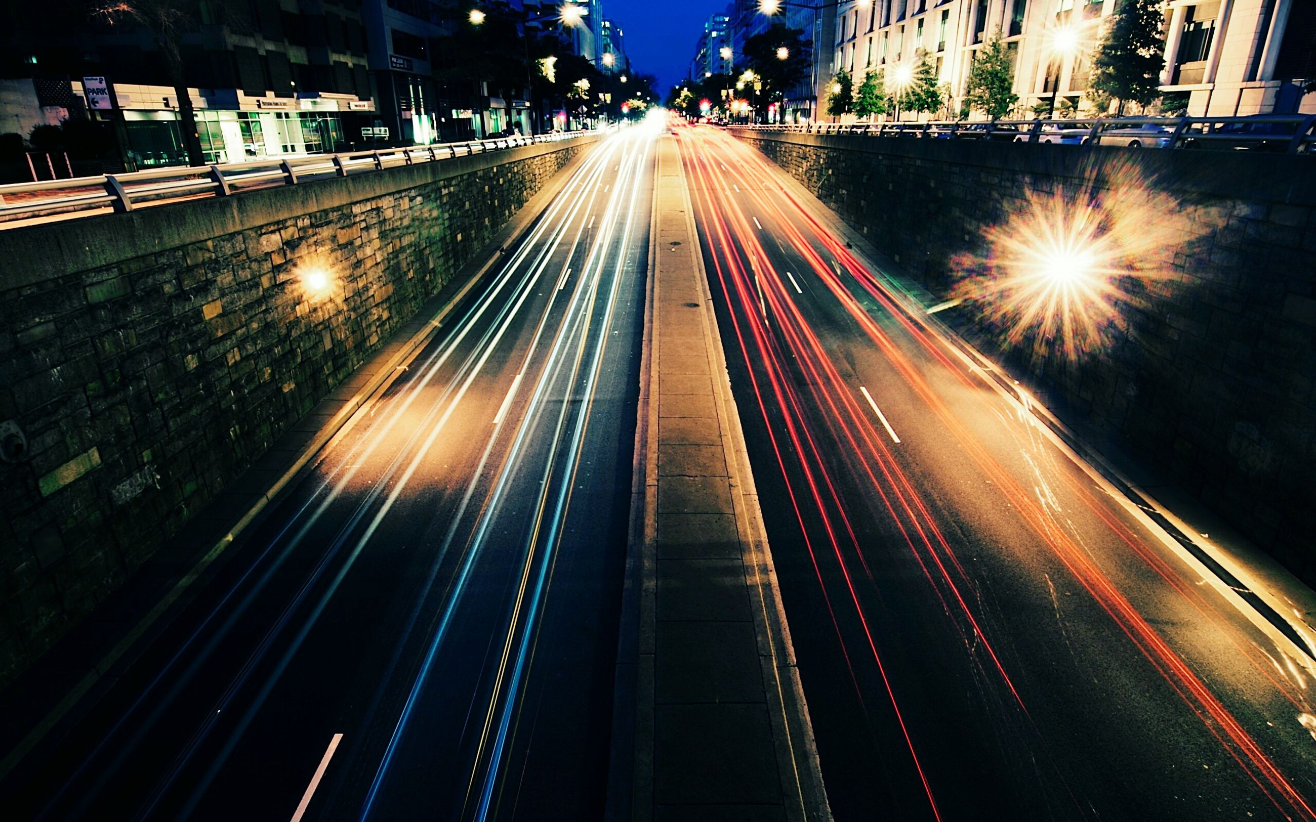 illuminated, transportation, night, speed, light trail, city, long exposure, street, traffic, motion, the way forward, architecture, built structure, lighting equipment, outdoors, car, road, city life, building exterior, land vehicle, no people, bridge - man made structure, sky, suspension bridge, cityscape, high street