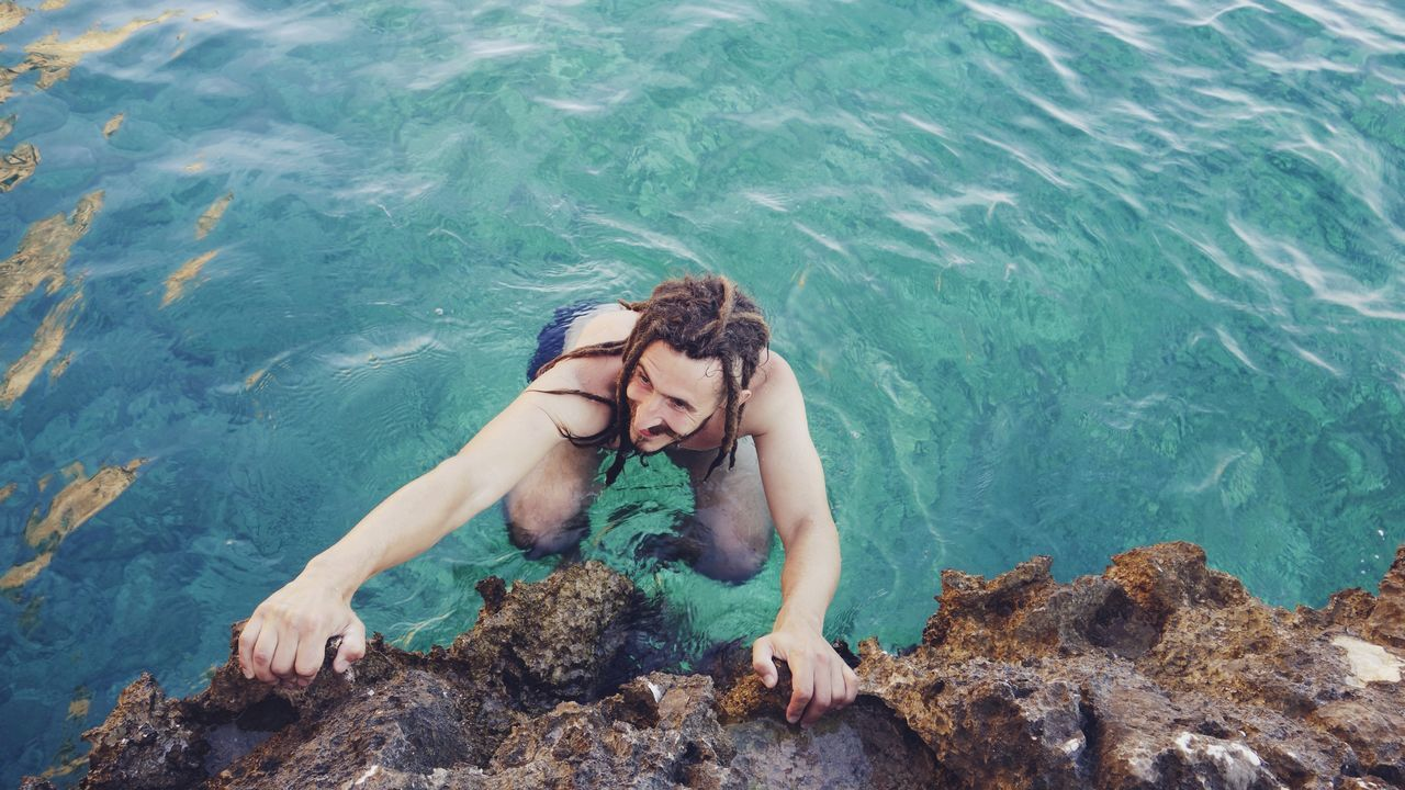 Blue Sea Bouldering Climbing Day Deep Water Soloing Dreadlocks Extreme Sports Happiness Happy High Angle View Man Ocean One Person Outdoors Rock Rock Climbing Sea Smiling Swimming Travel Travel Destinations Vacations Water Young Adult