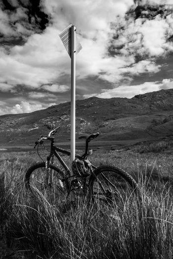 A bicycle leaning against a passing place marker somewhere in the Highlands of Scotland. Bicycle Landscape Landscape_photography Monochrome Monochrome Photography Mountain Outdoors Scotland Scottish Highlands Transportation
