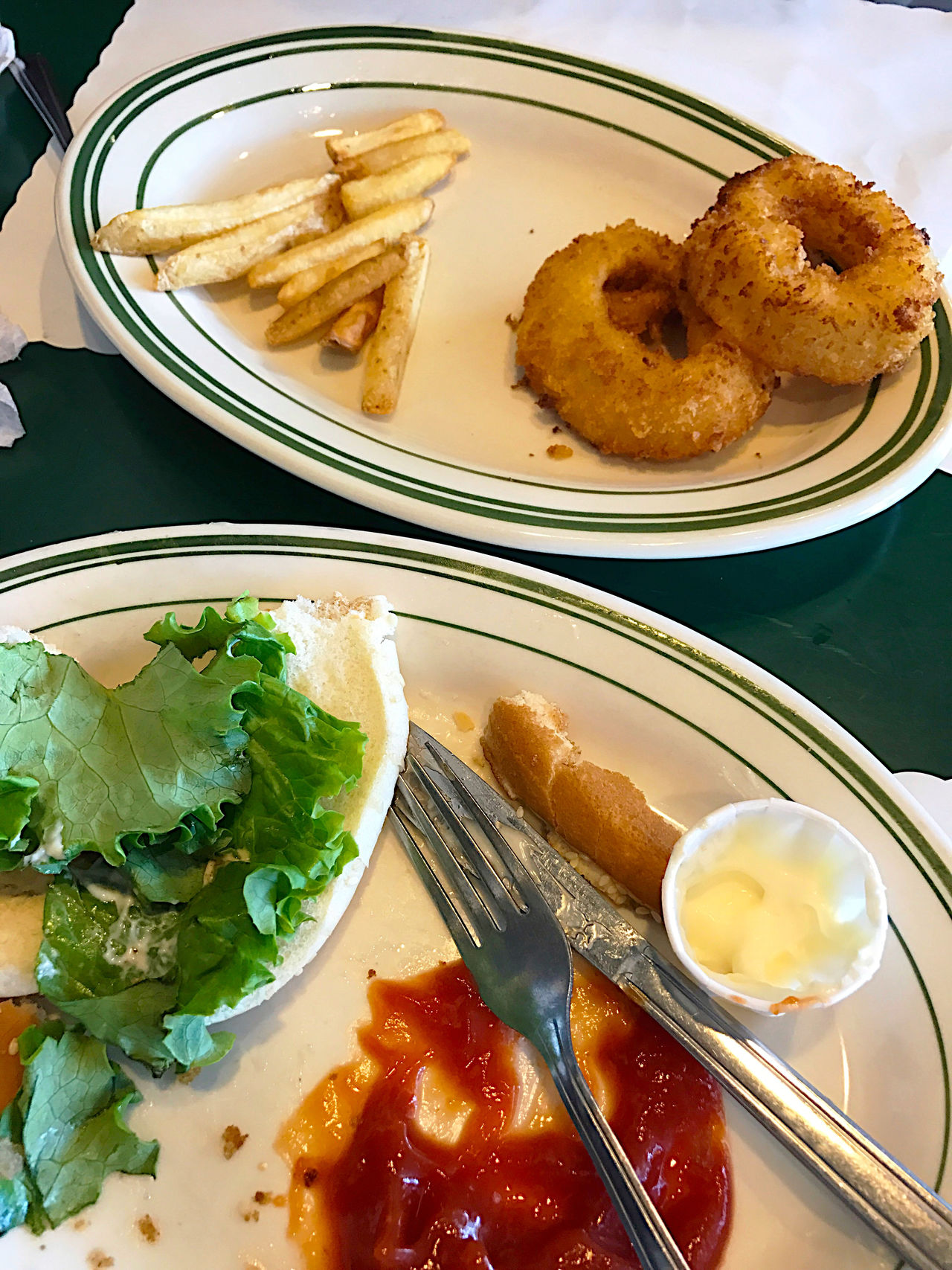 Condiments  Day Dinner Knife Dirty Dishes Eaten Finished Fork Fries Indoors  Ketchup Leftovers Lettuce Lunch Mayonnaise No People Onion Rings Overhead Phone Camera Platters Silverware  Table Textures