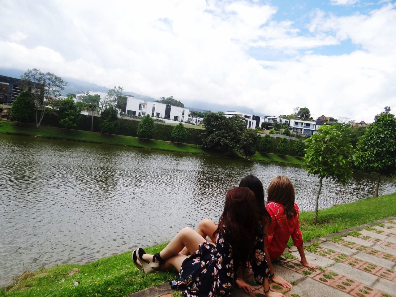 building exterior, real people, water, architecture, built structure, rear view, togetherness, day, two people, sitting, leisure activity, sky, cloud - sky, women, river, outdoors, casual clothing, tree, young women, full length, lifestyles, nature, city, young adult, men, grass, friendship, adult, people