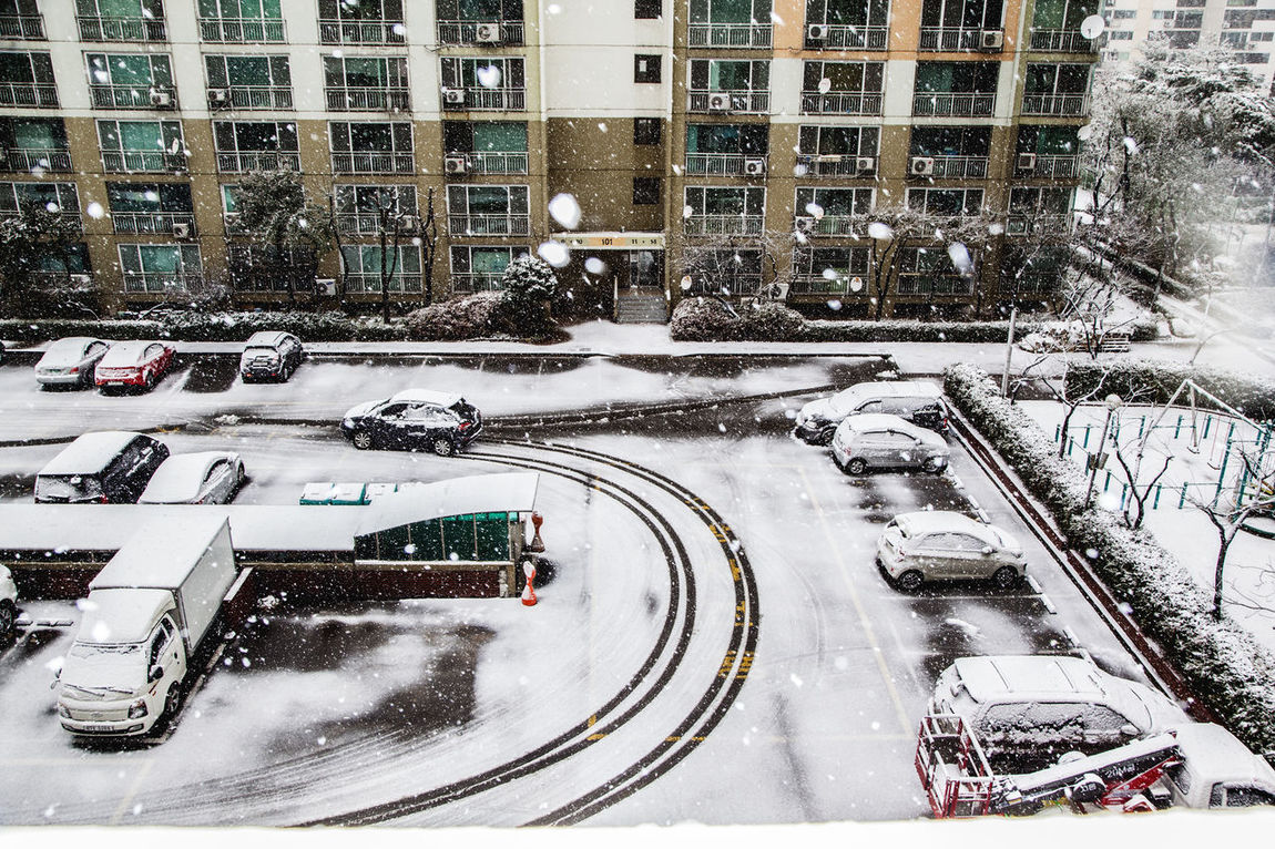 Apartment Architecture Building Exterior Car City City Life Cold Temperature Culture Famous Place Fountain Illuminated Motion Night Parking Lot Residential District Road Season  Showcase: December Snow Snowing Street Trail Urban Wildlife In Residential Area Winter