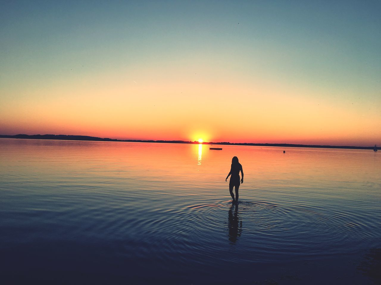 sunset, silhouette, scenics, tranquility, tranquil scene, reflection, nature, beauty in nature, full length, sky, copy space, idyllic, sea, one person, horizon over water, outdoors, sun, water, beach, clear sky, standing, real people, day, people