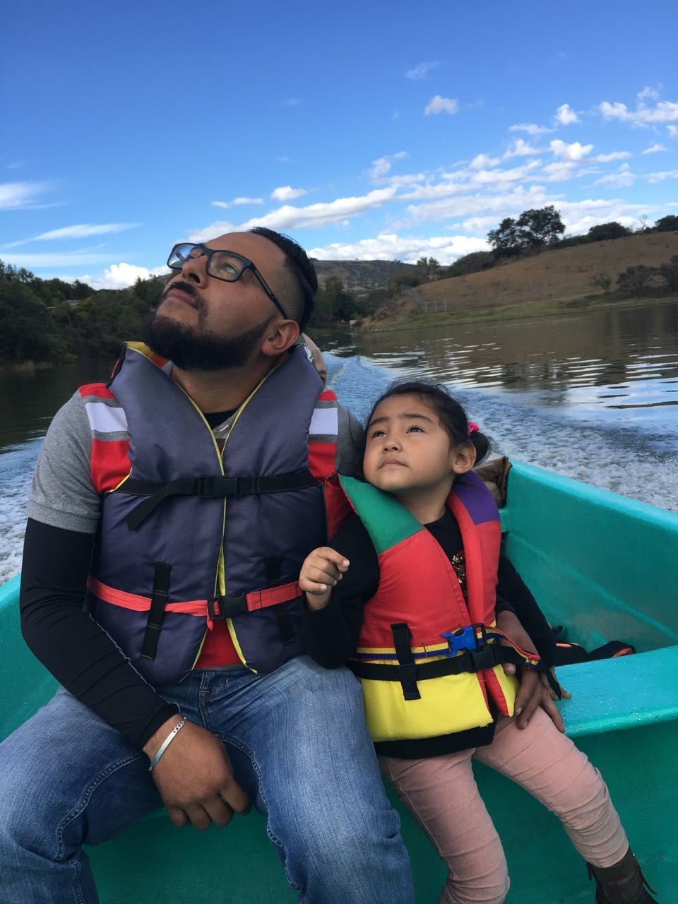 Father And Daughter Looking Up While Sitting On Boat In Lake Against Sky