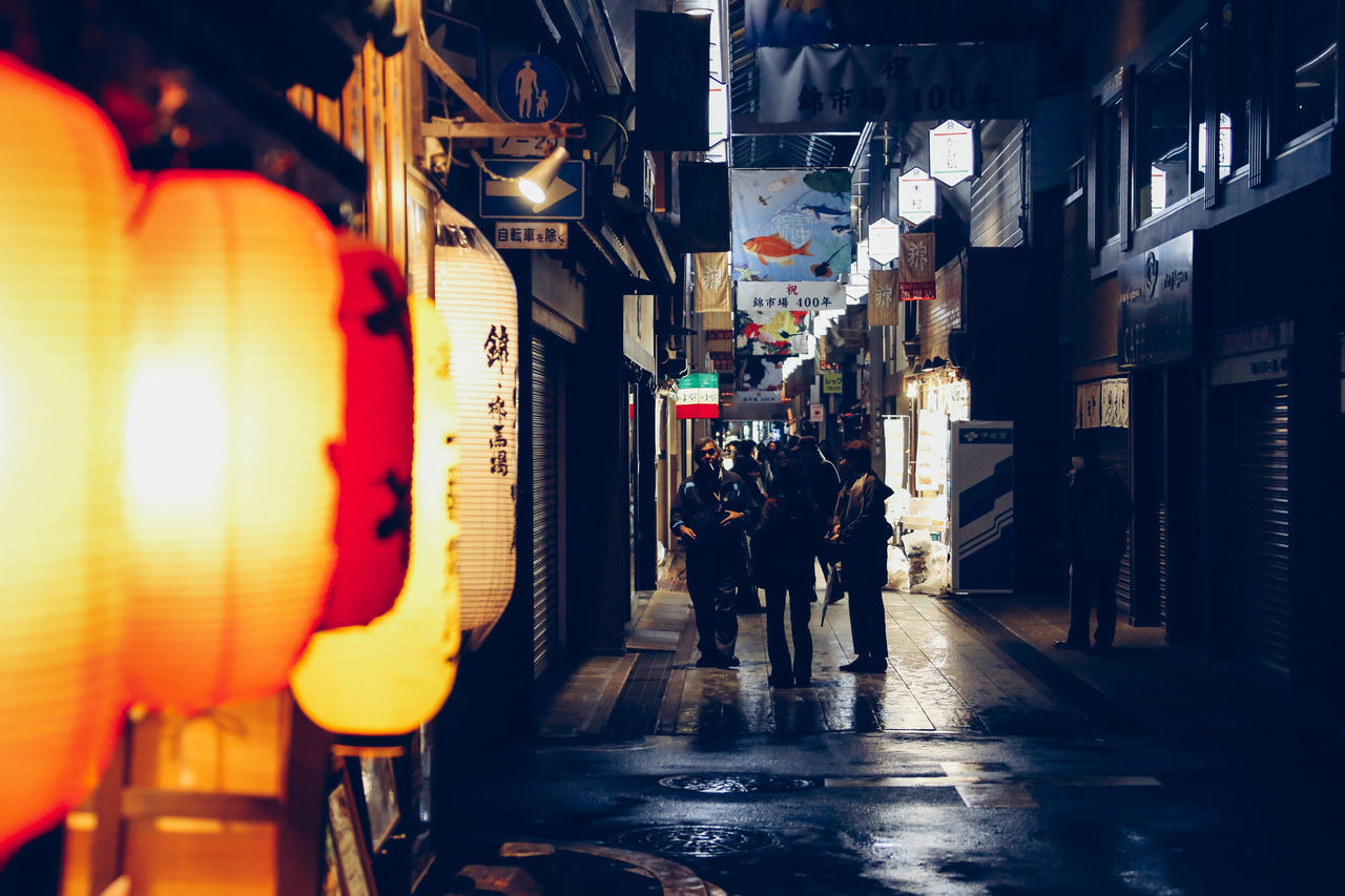 illuminated, night, men, walking, built structure, building exterior, real people, architecture, city, outdoors, women, people