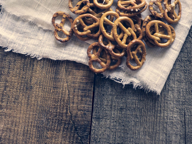 Heap of fresh Wheat salt pretzels on hessian linen fabric cloth and wooden table Close-up Cloth Fabric Fresh Heap Hessian Linen Man Made Object No People Pretzels Salt Table Tied Knot Wheat Wooden