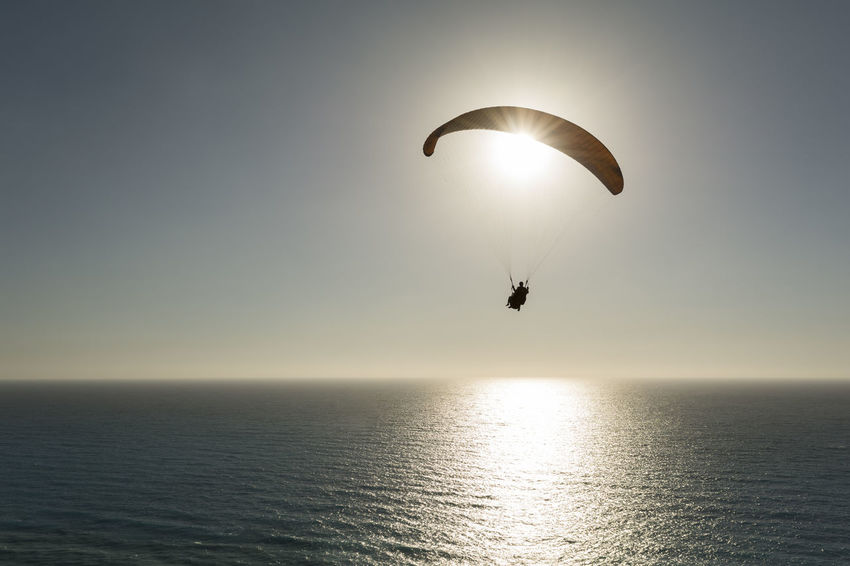 Silhouette of paraglider flying over the sea Free Freedom Fun Paragliding Sunlight Tranquility Vitality Action Activity Adventure Extreme Sports Flight Flying Hobby Horizon Outdoors Parachute Paraglider Paragliding Sea Silhouette Sky Soaring Sun Tranquil Scene