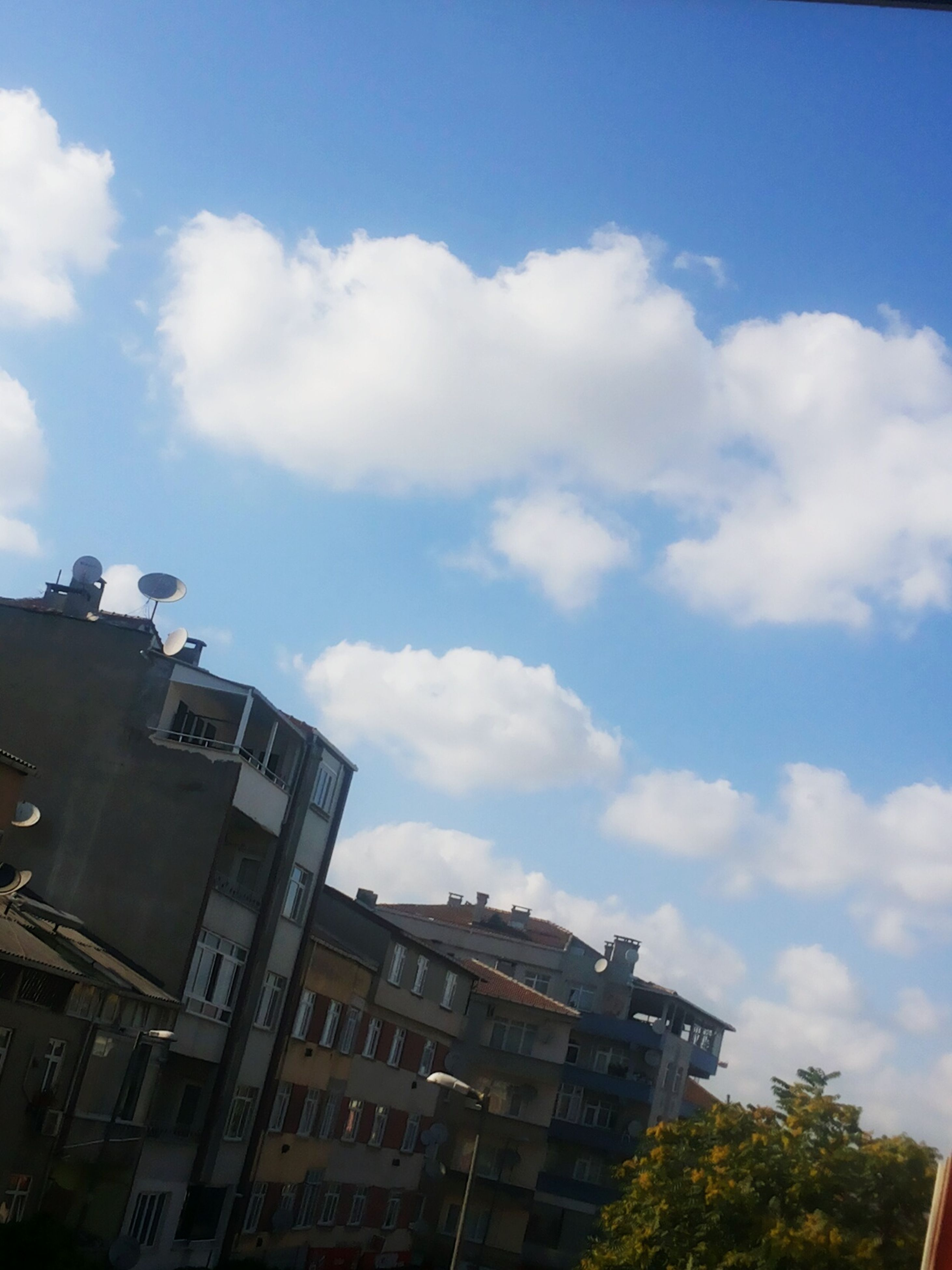 building exterior, architecture, built structure, sky, low angle view, cloud - sky, residential building, residential structure, blue, cloud, building, house, city, day, outdoors, cloudy, no people, high section, sunlight, window