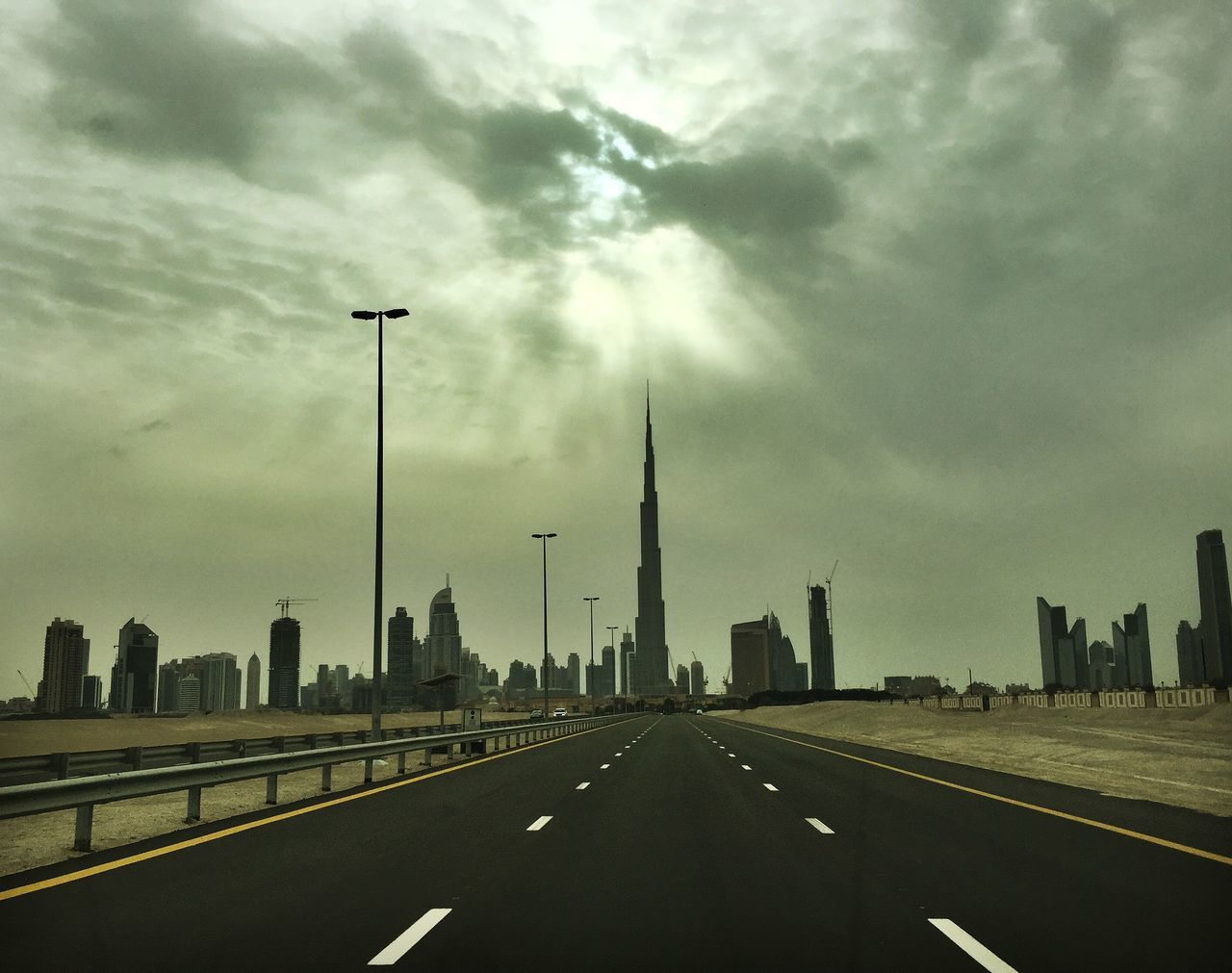 architecture, built structure, sky, city, road, transportation, travel destinations, skyscraper, cloud - sky, the way forward, building exterior, no people, modern, outdoors, day, cityscape, urban skyline