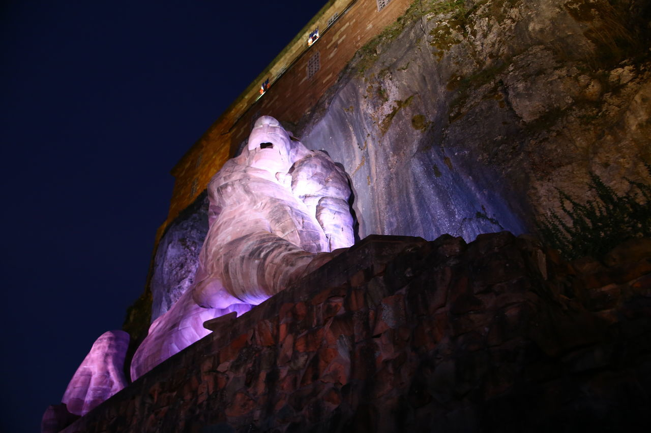 low angle view, human representation, rock formation, night, illuminated, no people, sculpture, statue, cave, indoors, nature, sky, close-up