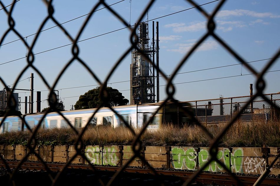 Fence Chainlink Fence Barbed Wire Protection Sky No People Industry Outdoors Grass Architecture Day Refinery Train Public Transportation Melbourne Pollution Muttlypictures Industrial Landscapes Altona North Refinery Grafitti Train Tracks