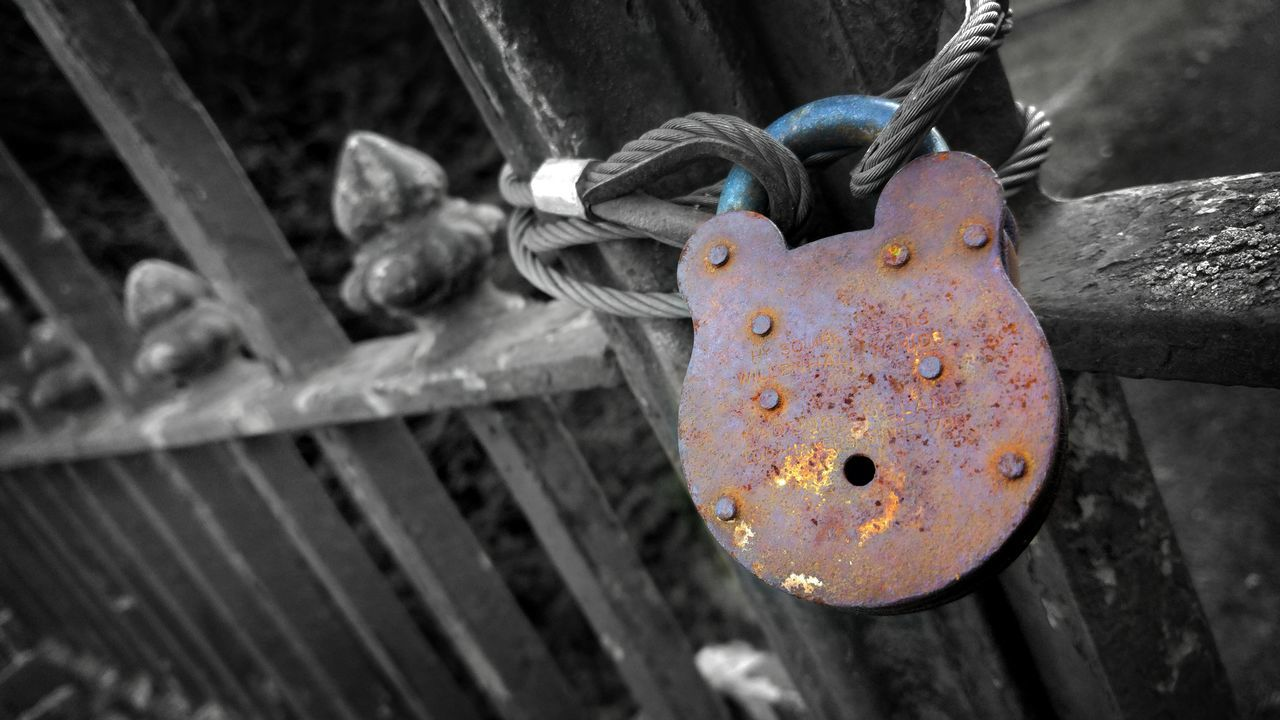 Close-Up Of Rusty Padlock Hanging On Fence