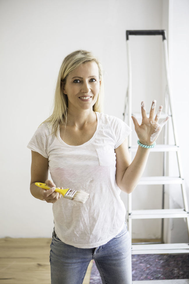 Portrait of a young lady in a yoga studio doing some renovations Beauty Casual Clothing DIY Front View Hand Ladder Leisure Activity Lifestyles Long Hair Paint Portrait Renovations Single Standing Three Quarter Length White Yoga Studio Young Lady