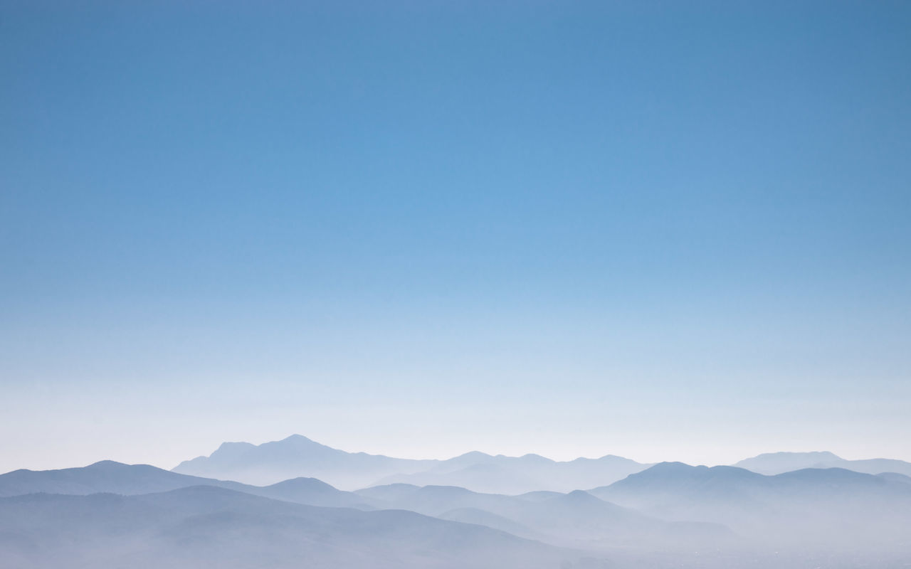 Scenic View Of Mountains Against Clear Sky During Foggy Weather