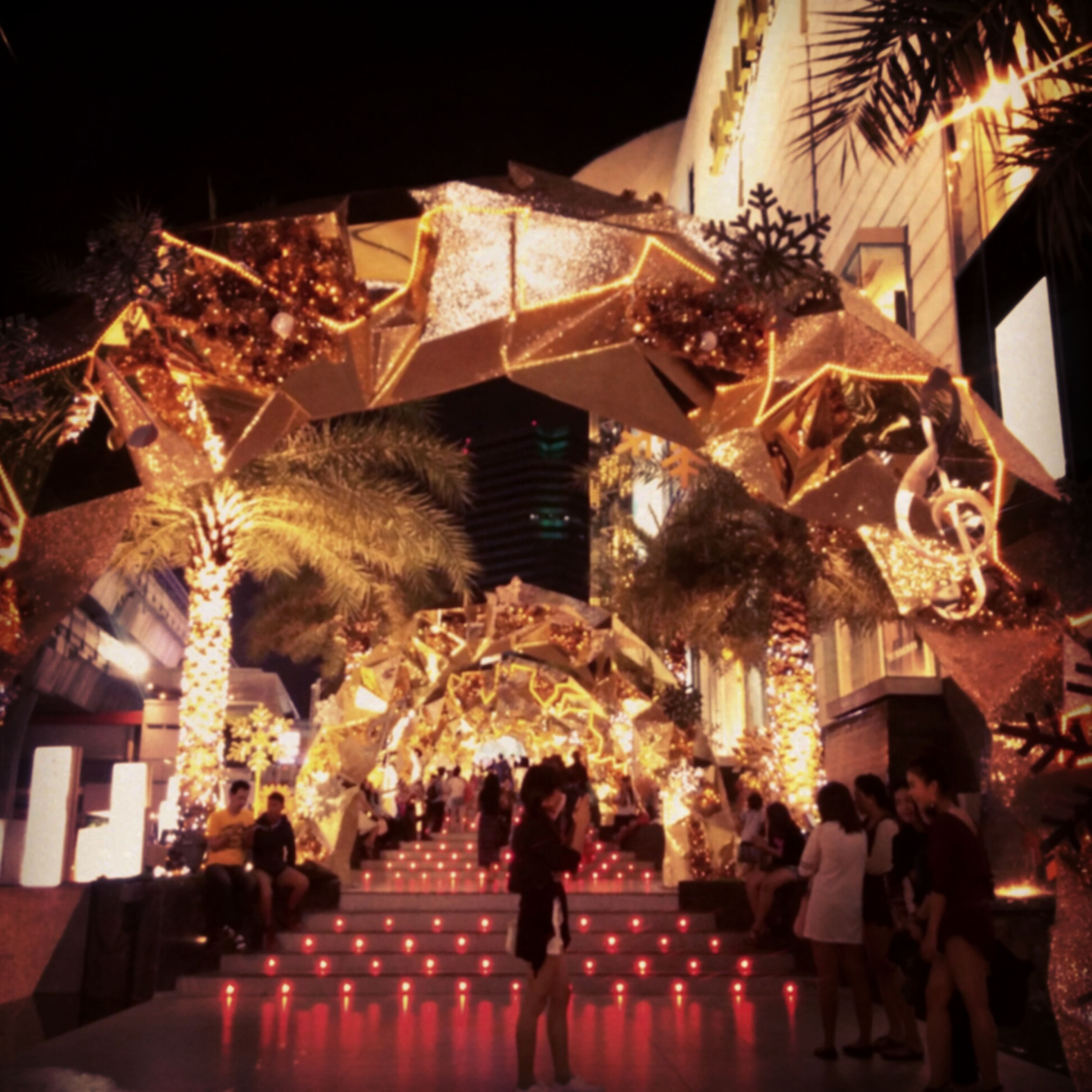 illuminated, night, celebration, built structure, men, lighting equipment, architecture, arts culture and entertainment, building exterior, lifestyles, leisure activity, person, decoration, low angle view, event, indoors, tradition, hanging, light - natural phenomenon