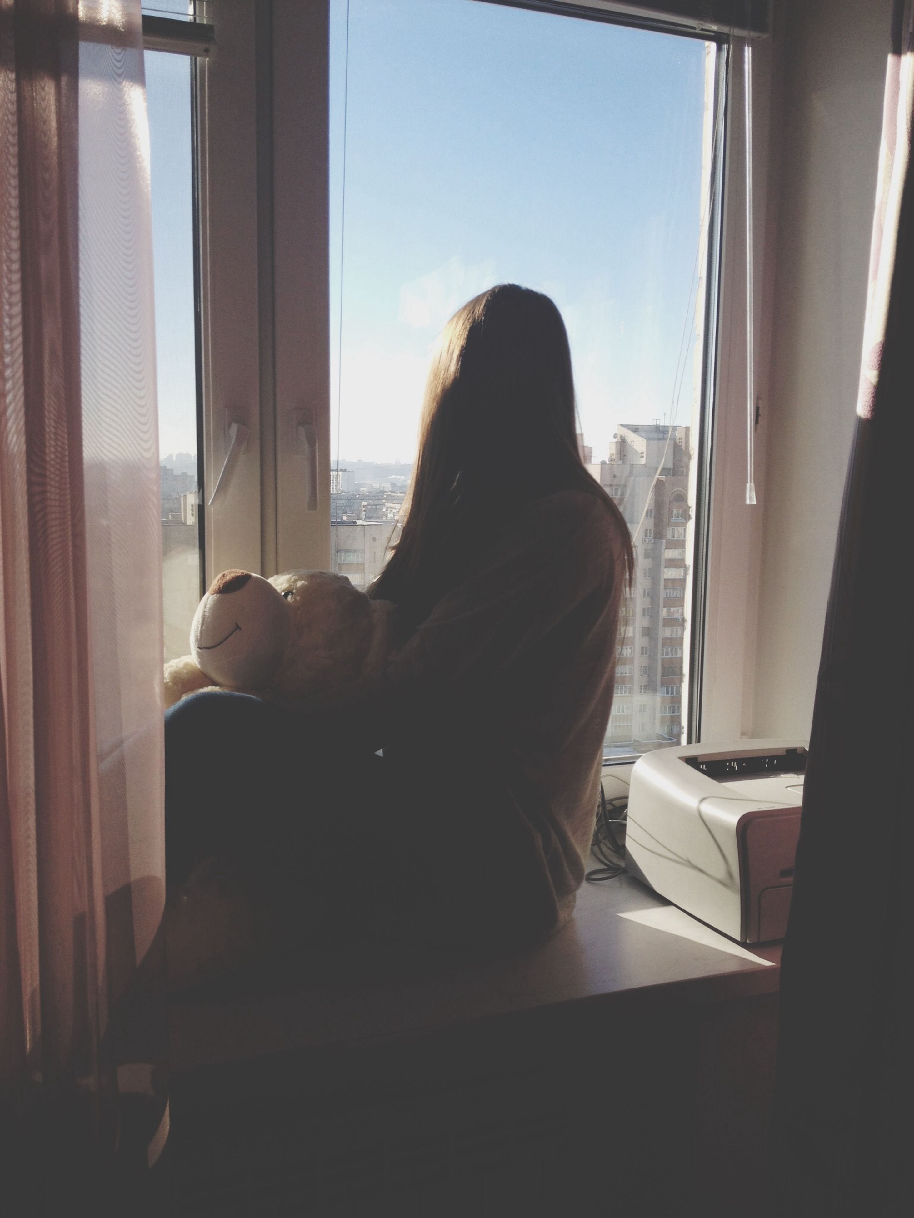 indoors, window, home interior, looking through window, lifestyles, sitting, rear view, glass - material, curtain, transparent, leisure activity, relaxation, domestic room, domestic life, person, waist up, long hair, casual clothing