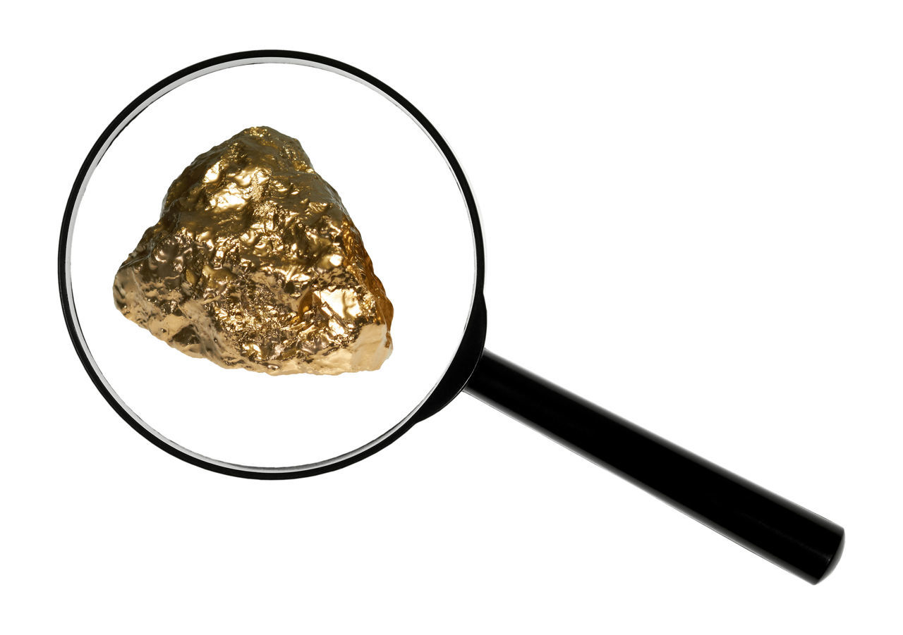 Close-Up Of Gold Nugget Seen Through Magnifying Glass Against White Background