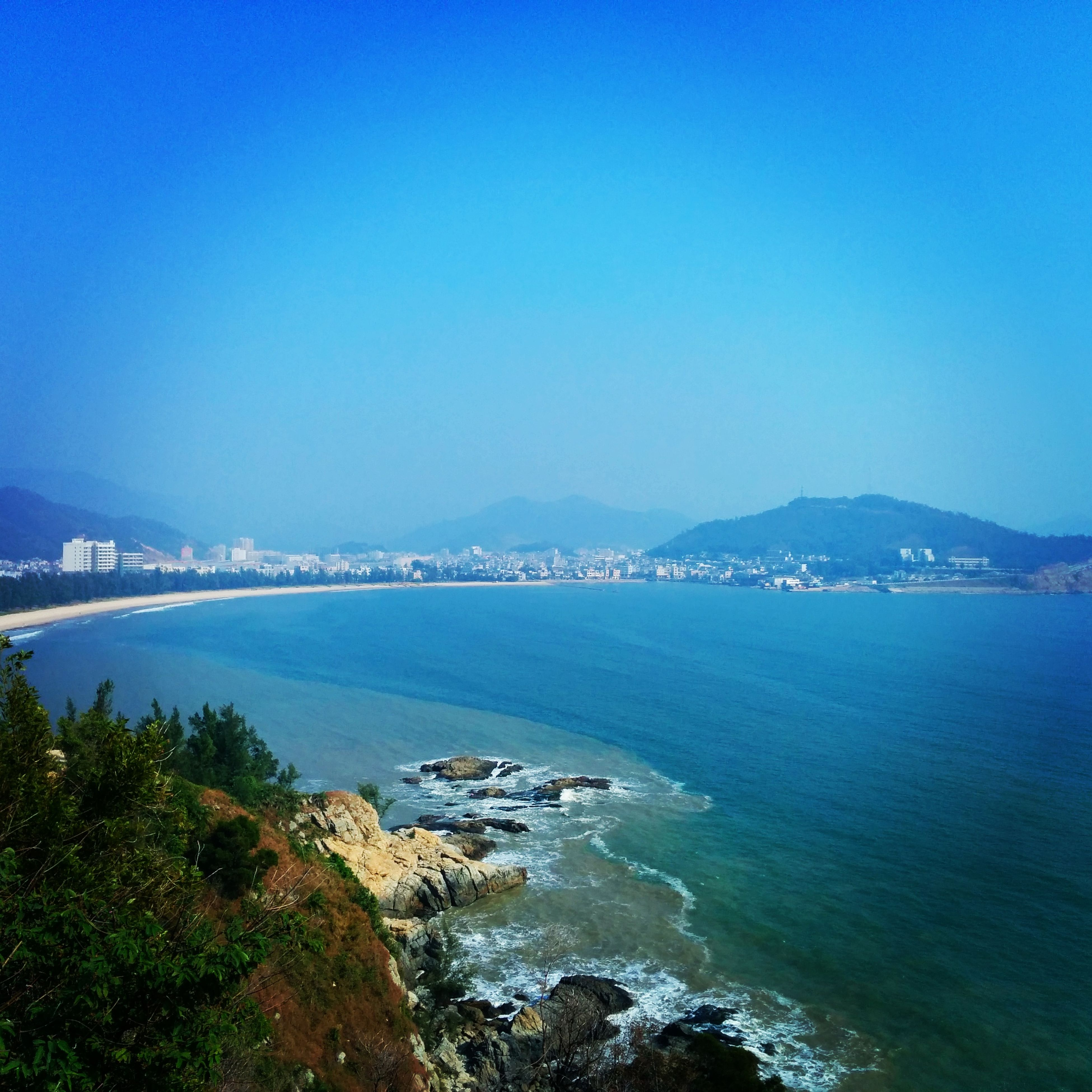 sea, water, blue, clear sky, copy space, scenics, coastline, mountain, beauty in nature, tranquil scene, tranquility, nature, built structure, beach, architecture, city, high angle view, waterfront, building exterior, shore