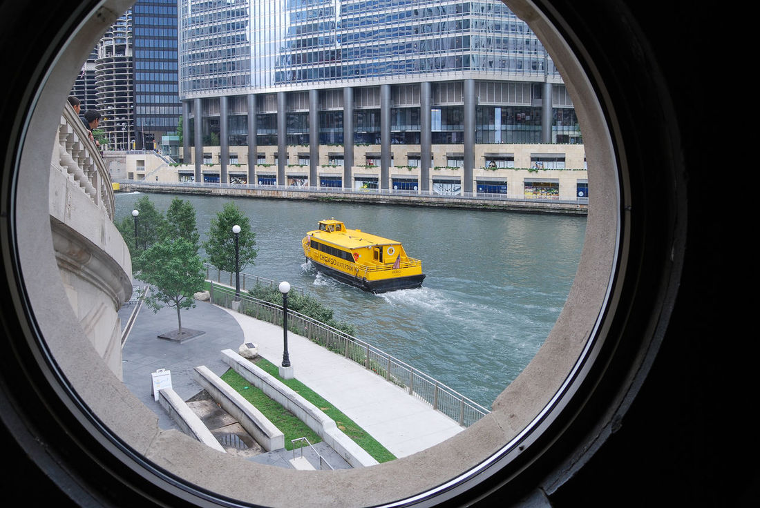 Look through the window of the old bridgehouse at Michigan Ave bridge onto the Chicago River where a water taxi passes by. Architecture Bridgehouse Bullseye Chicago Chicago River Chicago River Museum City City Life Geometric Shape Green Color Look Through The Window McCormick Bridgehouse Michigan Ave Bridge Michigan Avenue Water Taxi Yellow