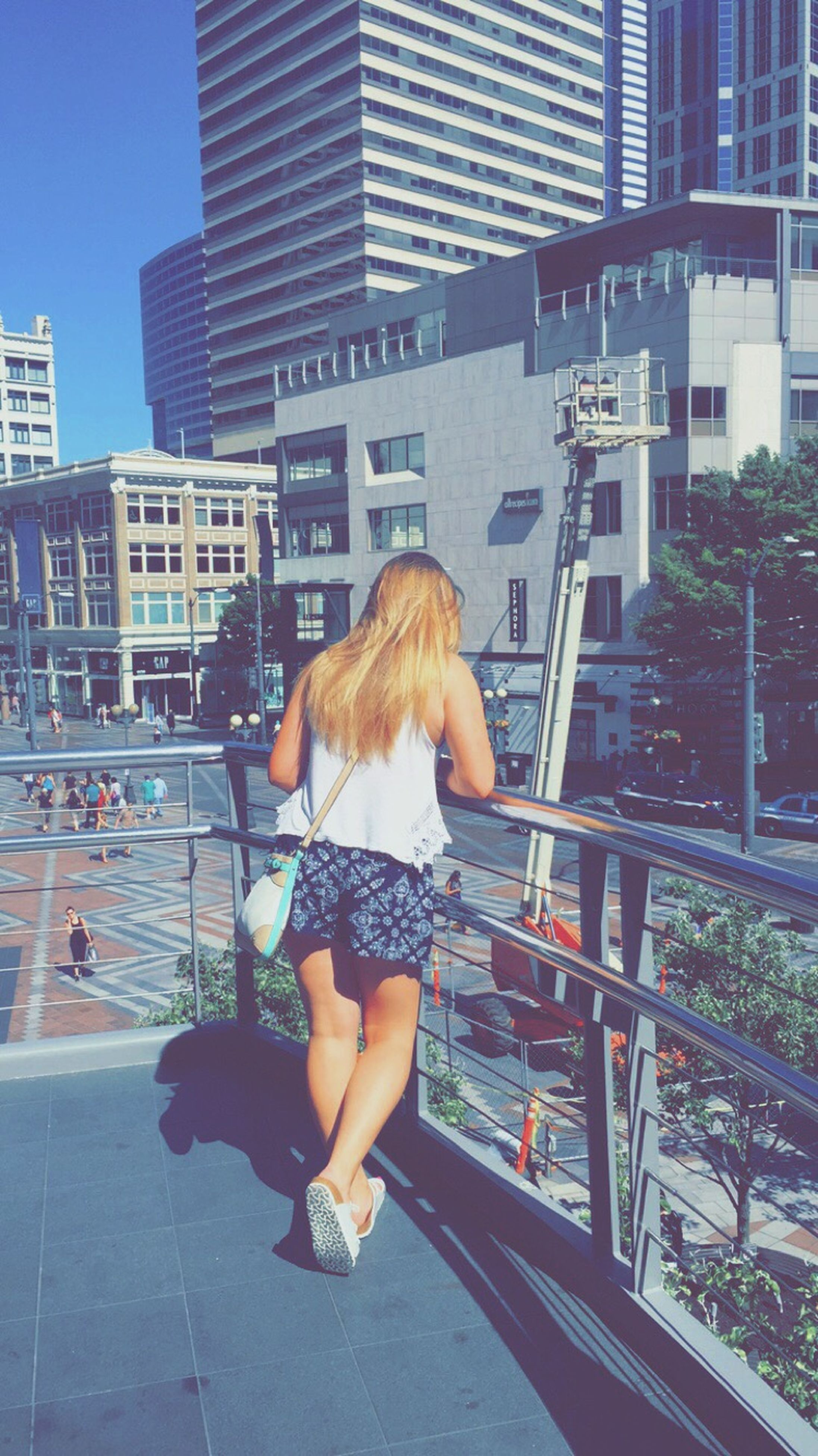 building exterior, lifestyles, architecture, leisure activity, built structure, city, full length, casual clothing, person, rear view, city life, water, young adult, young women, sitting, standing, outdoors, men