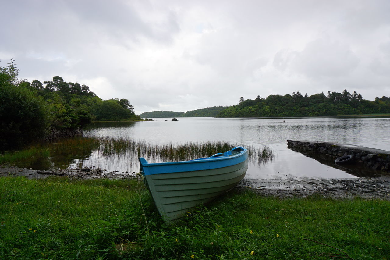A boat on the lake shore in Connemara, Ireland Beauty In Nature Blue Boat Boat Cloud - Sky Cloudy Day Day Grass Green Color Lake Lakeshore Moored Nature Nautical Vessel No People Outdoors Scenics Sky Tranquil Scene Tranquility Water White Boat