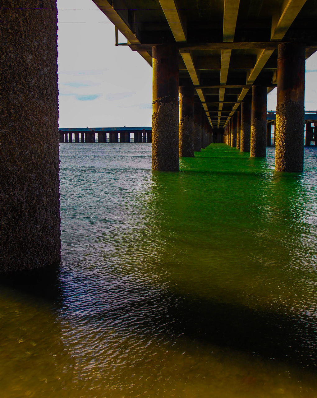 architecture, bridge - man made structure, underneath, built structure, connection, water, below, pier, river, architectural column, covered bridge, bridge, no people, waterfront, outdoors, under, nature, day, sky