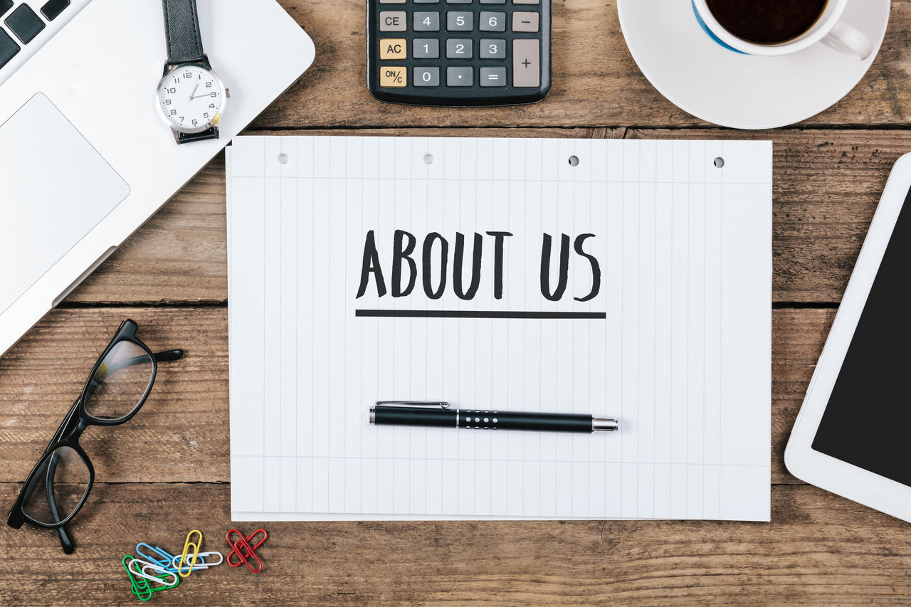 About Us written on note book on office desk About Close-up Desk Desk Desktop High Angle View Job No People Note Book Note Pad Office Paper Pen Table Wireless Technology Wood - Material Working Writing