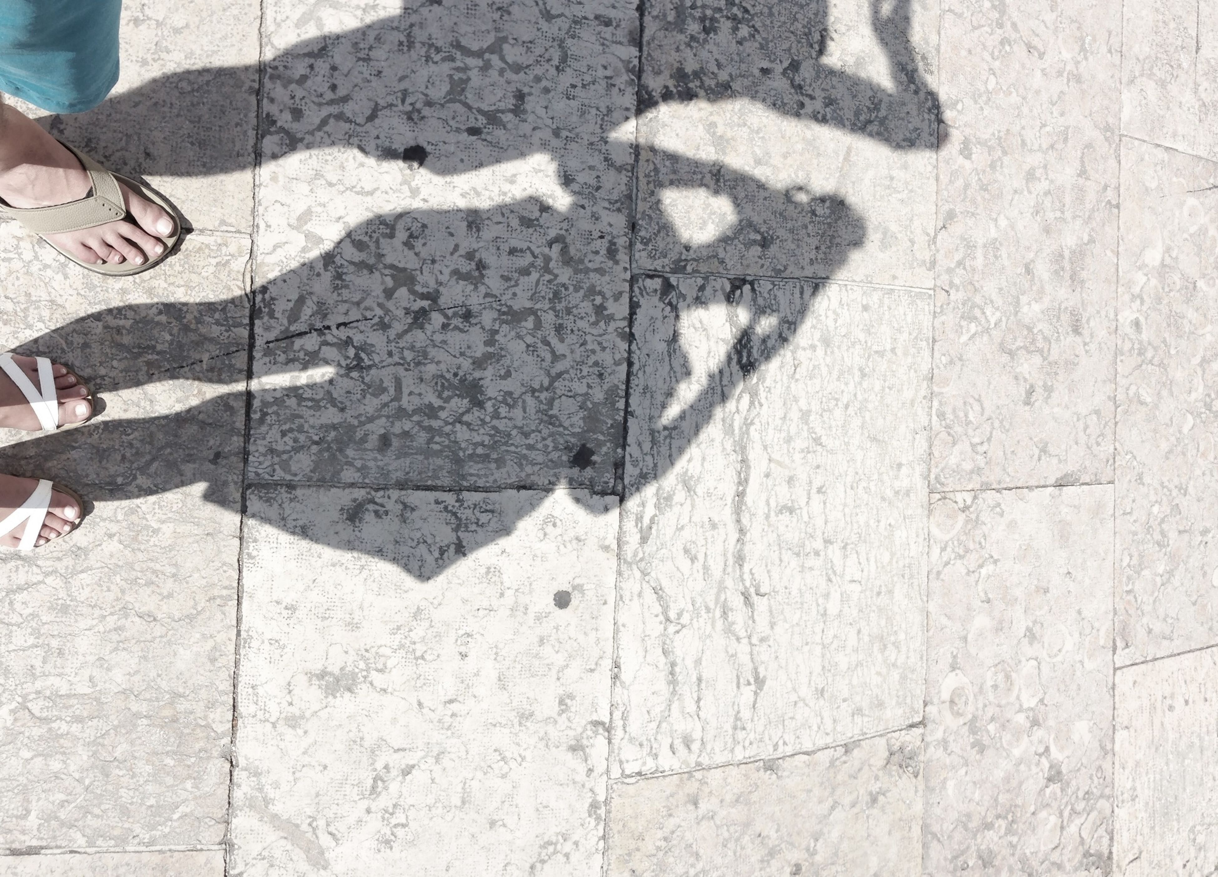 low section, lifestyles, person, leisure activity, men, standing, pattern, high angle view, unrecognizable person, human foot, textured, part of, shadow, wall - building feature, shoe